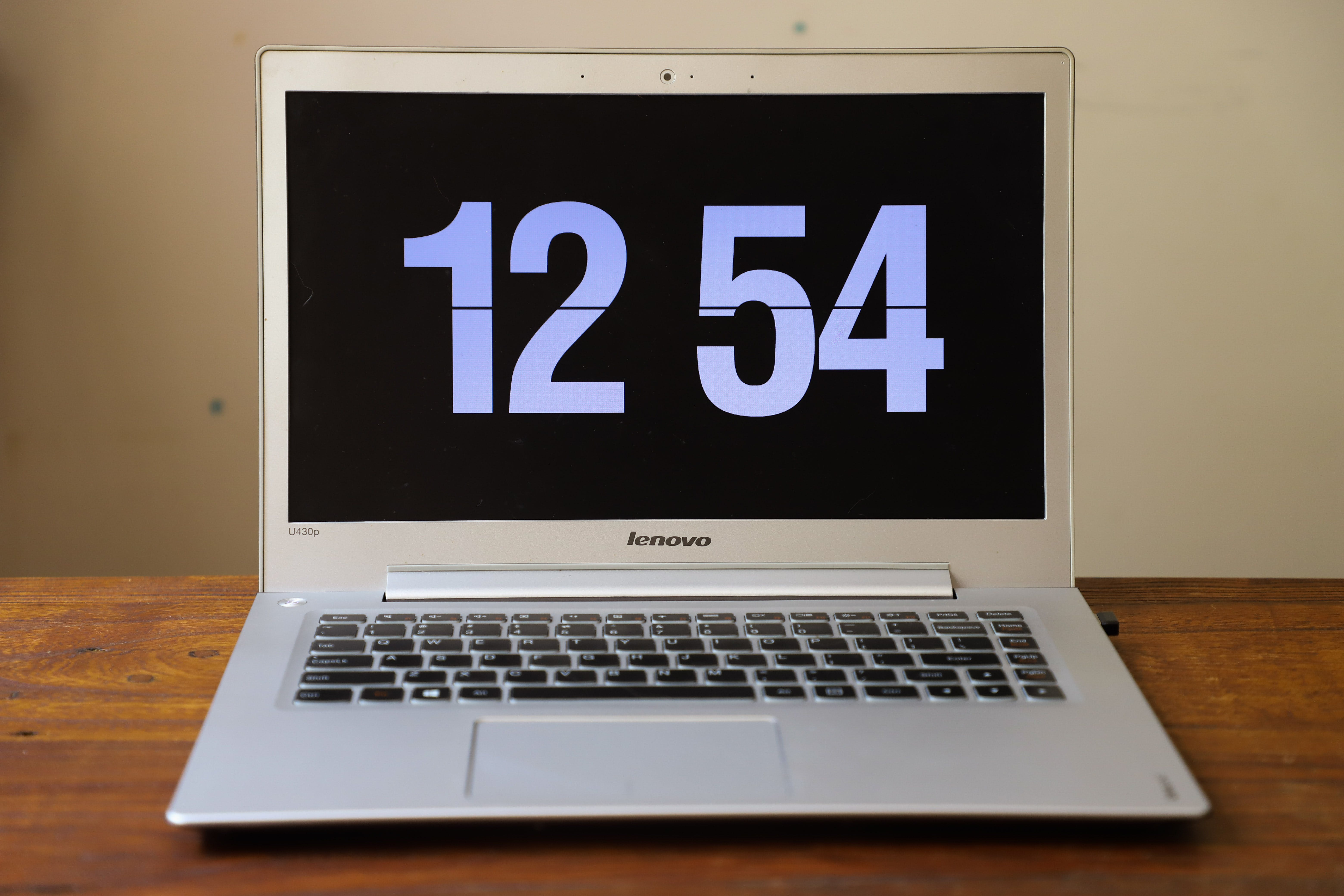 Turned-on Silver Lenovo Laptop Displaying Clock at 12:54
