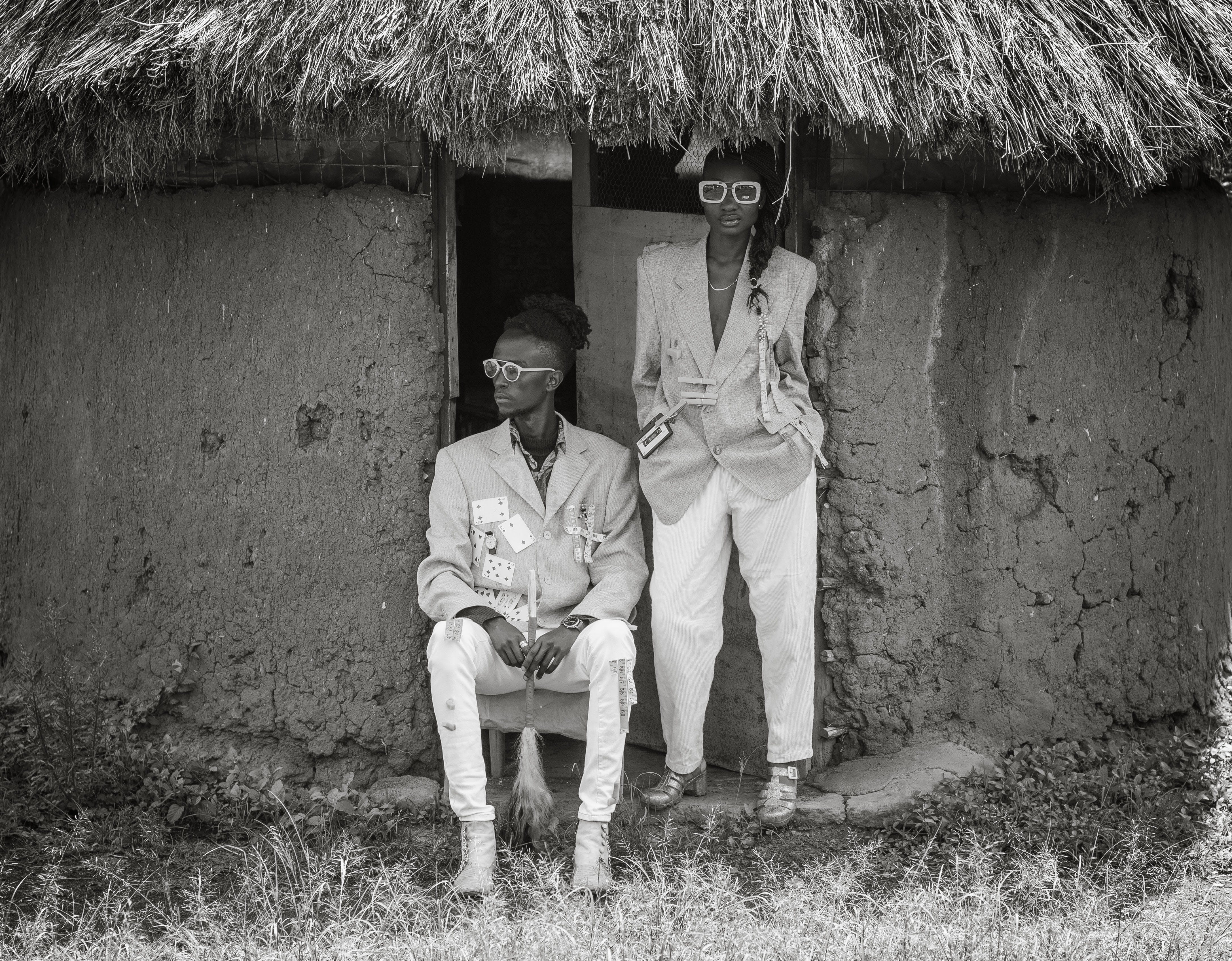 Grayscale Photo of Man and Woman Wearing Suit Beside Concrete House