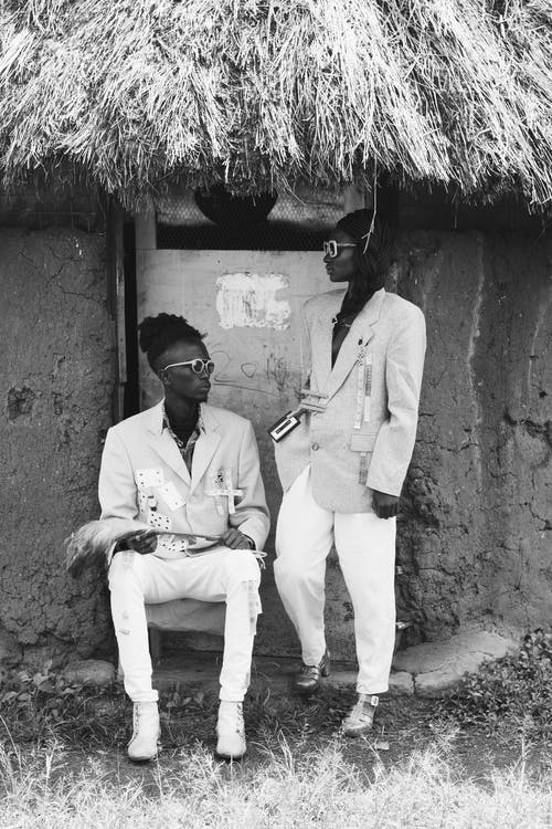 Grayscale Photo of Two Men Standing Near Hut