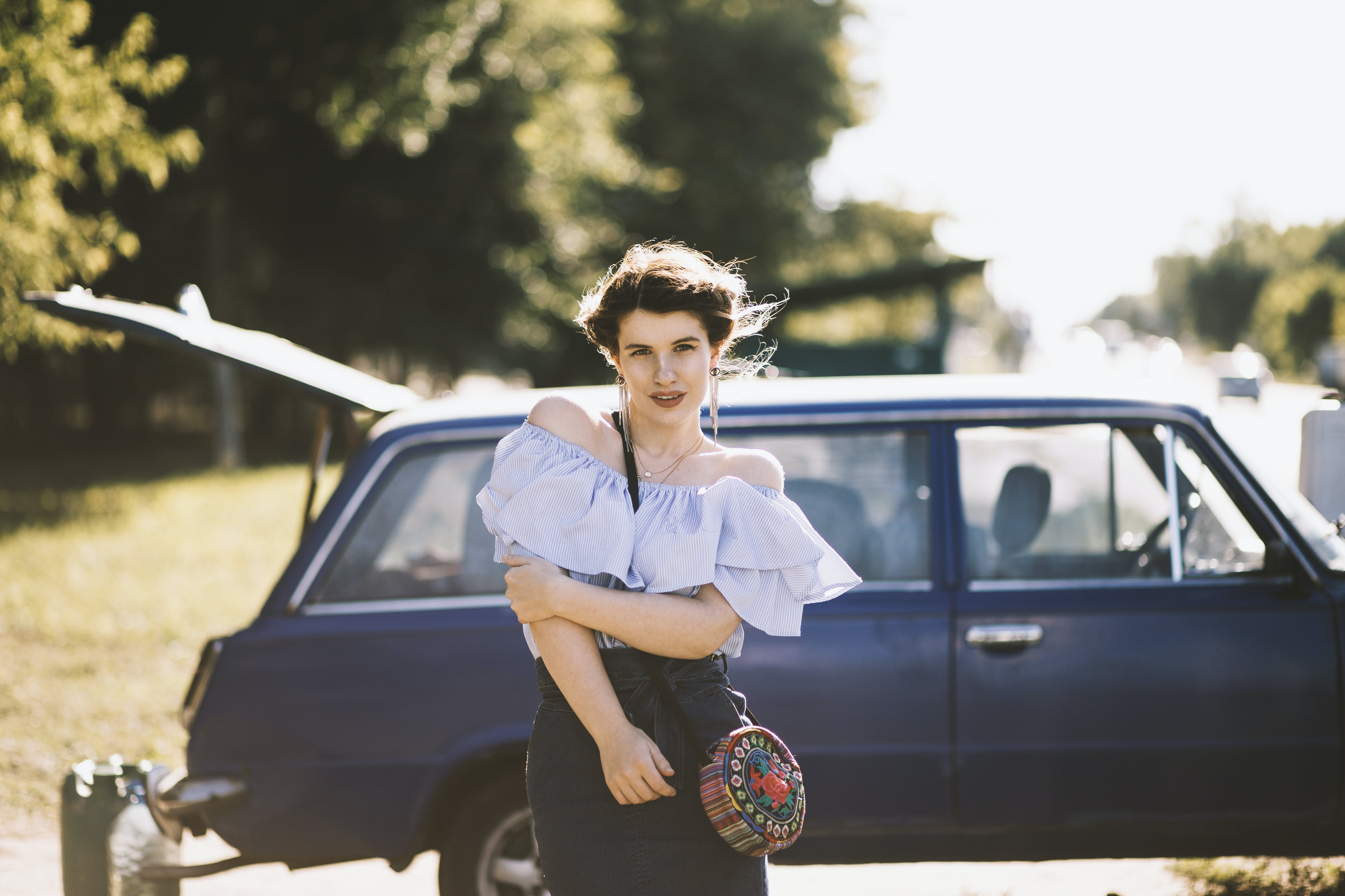 Woman Standing Near Blue Vehicle