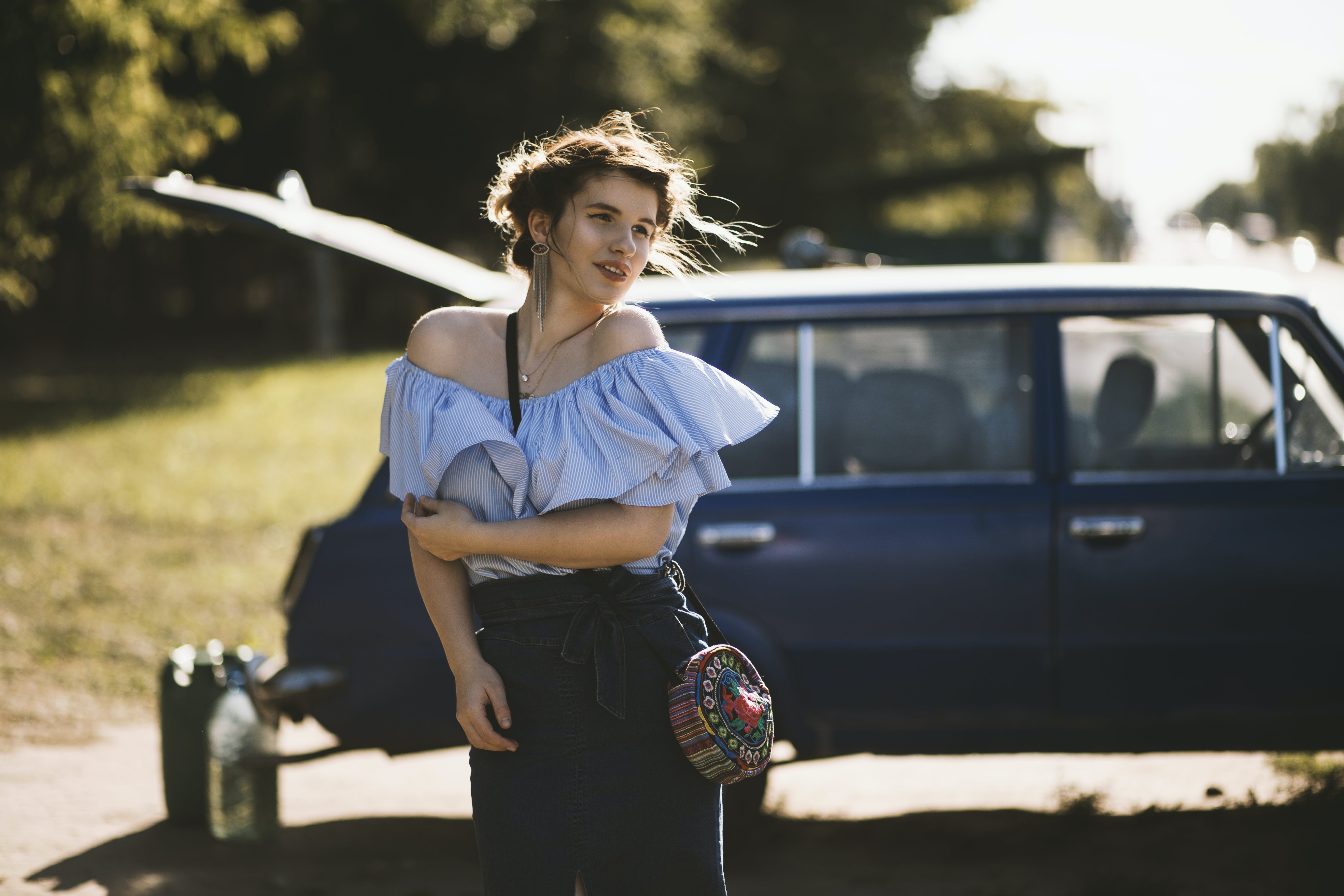 Woman in Blue Blouse Standing Near Blue Station Wagon