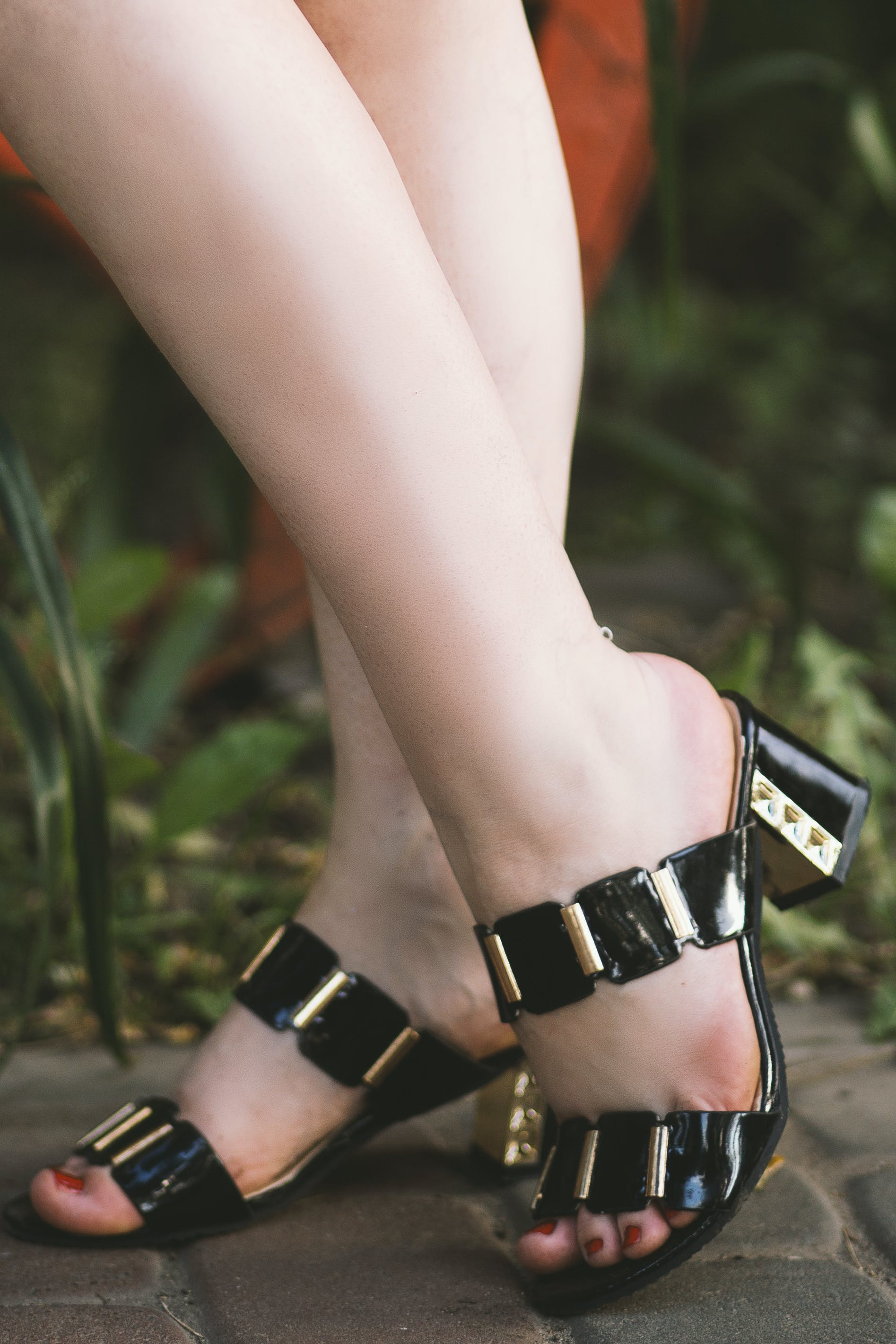 Woman Wearing Pair of Black-and-gold Open-toe Sandals