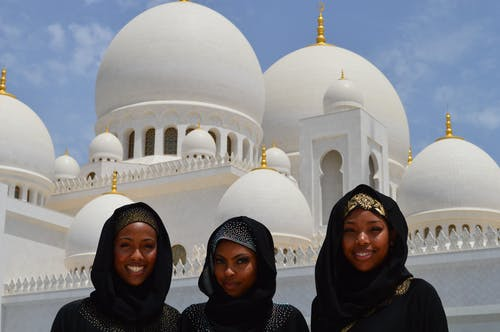 Three Women Taking A Photo In Front Of White Mosque