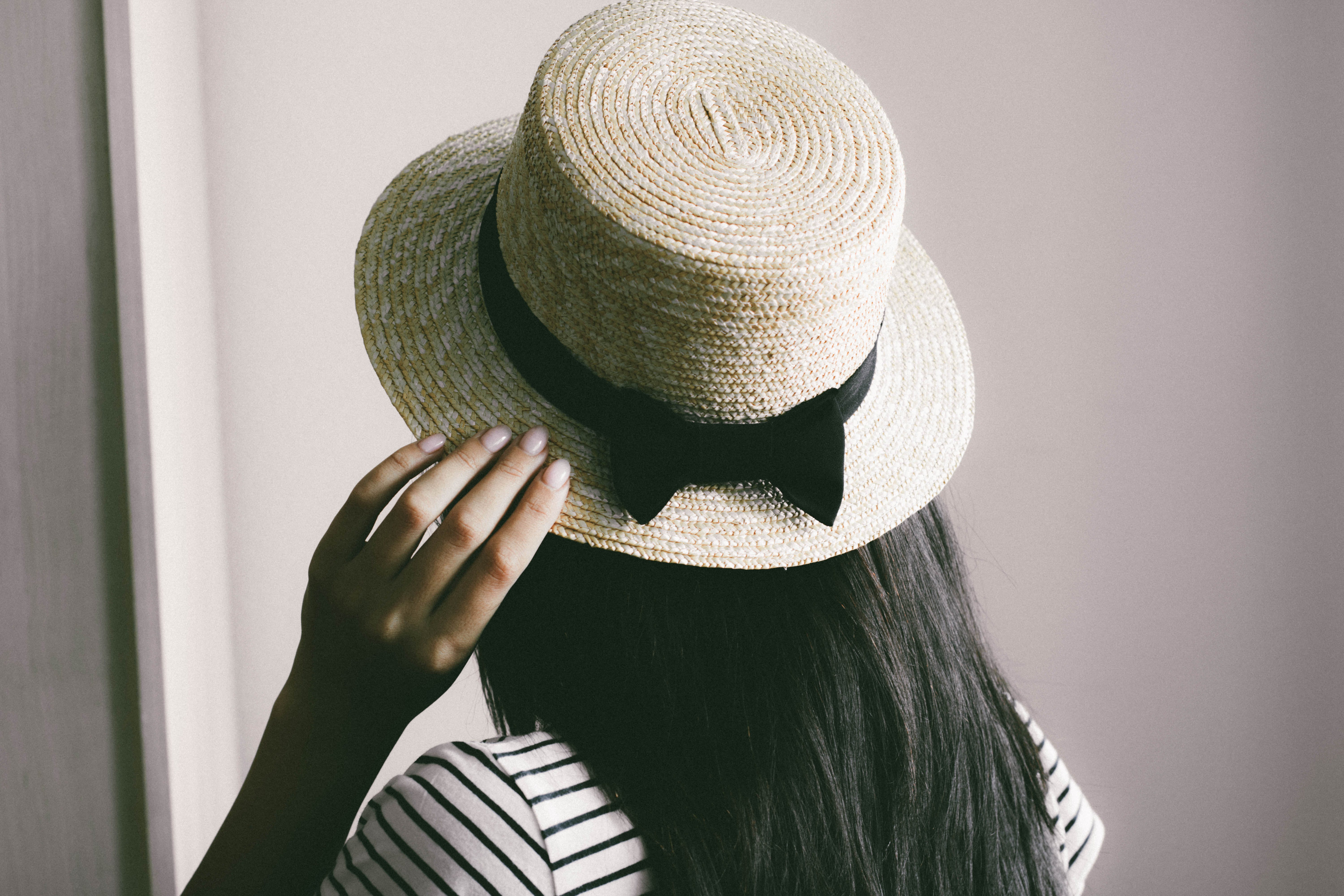 Person Holding Brown Straw Hat