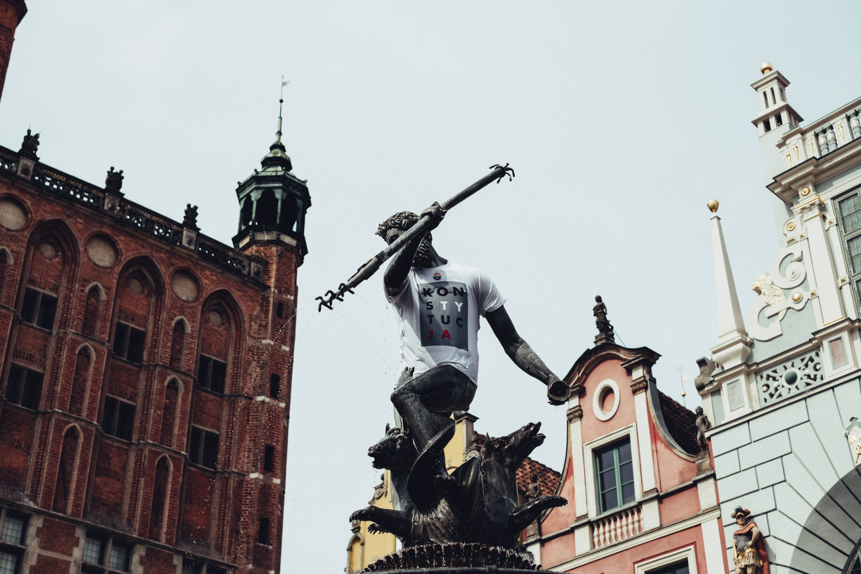 Man's Profile Holding Sphere Statue Near Concrete Buildings