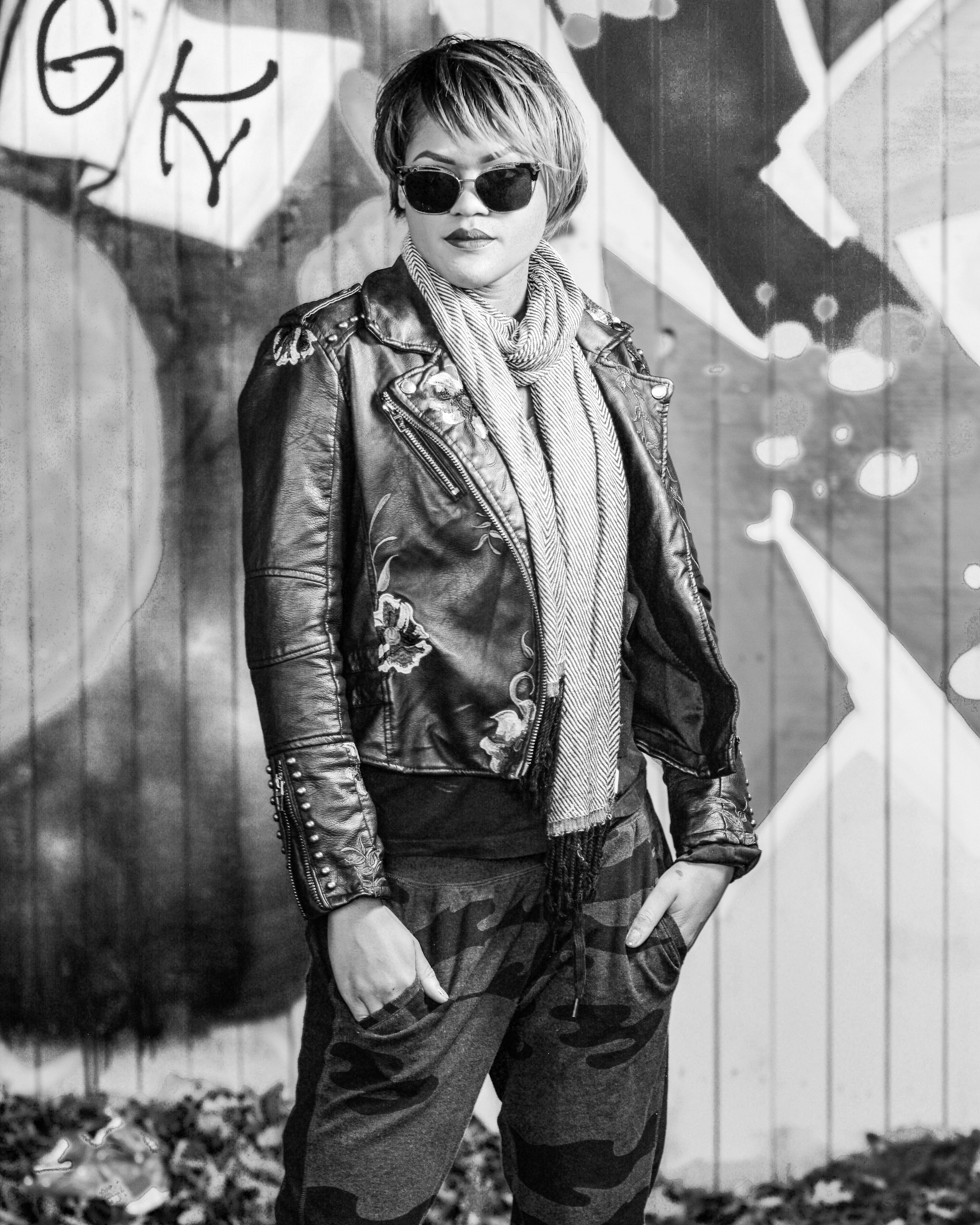 Grayscale Photo of Posing Woman and Holding Pocket Wearing Scarf and Leather Jacket