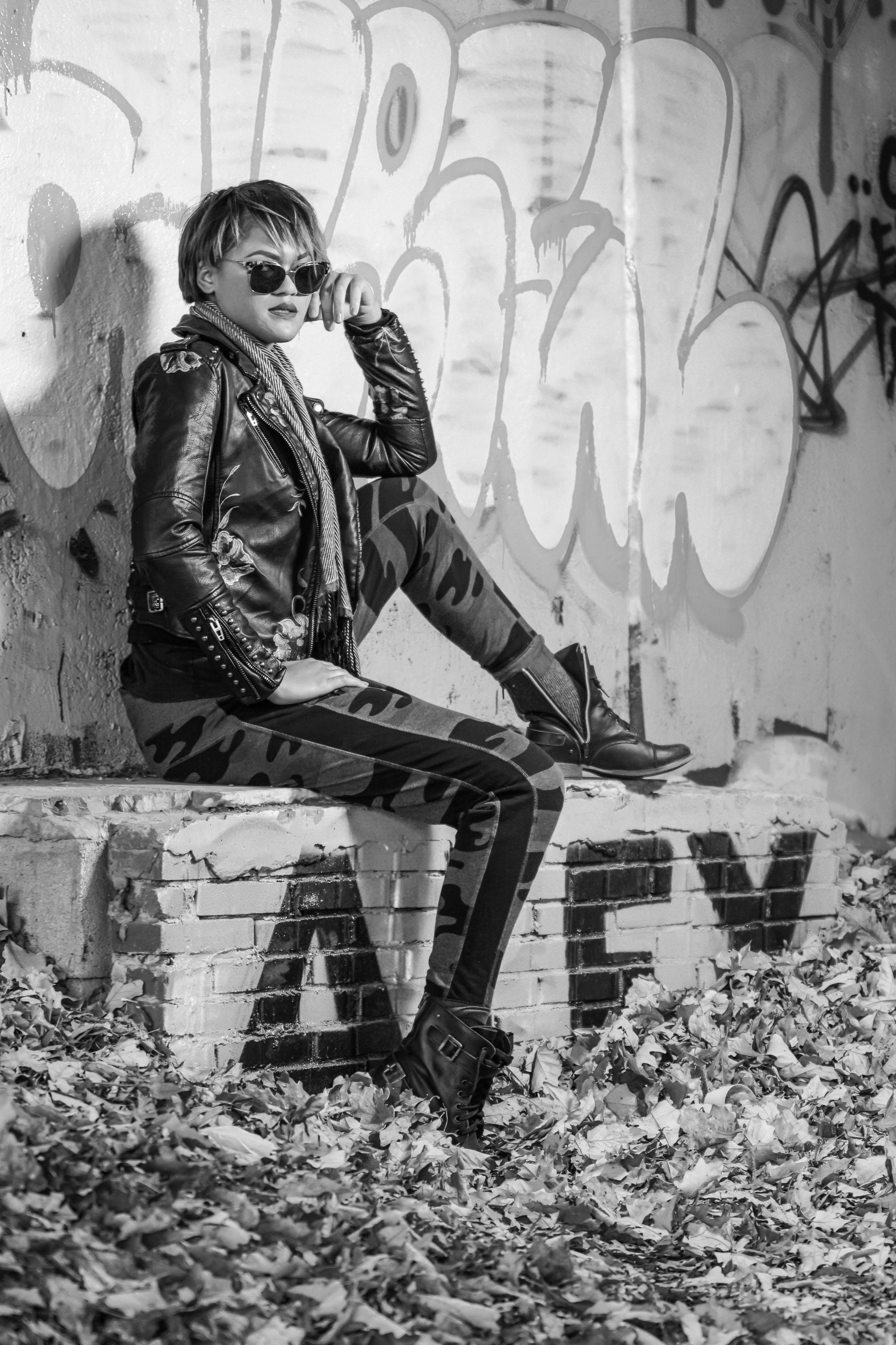 Grayscale Photo of Woman Sitting on Concrete