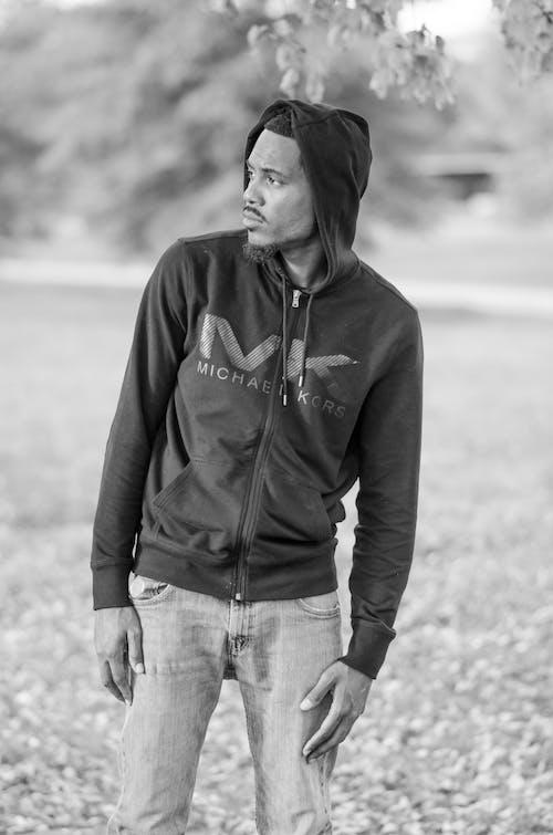 Grayscale Photo of Man Wearing Michael Kors Zip Hoodie Looking on Left