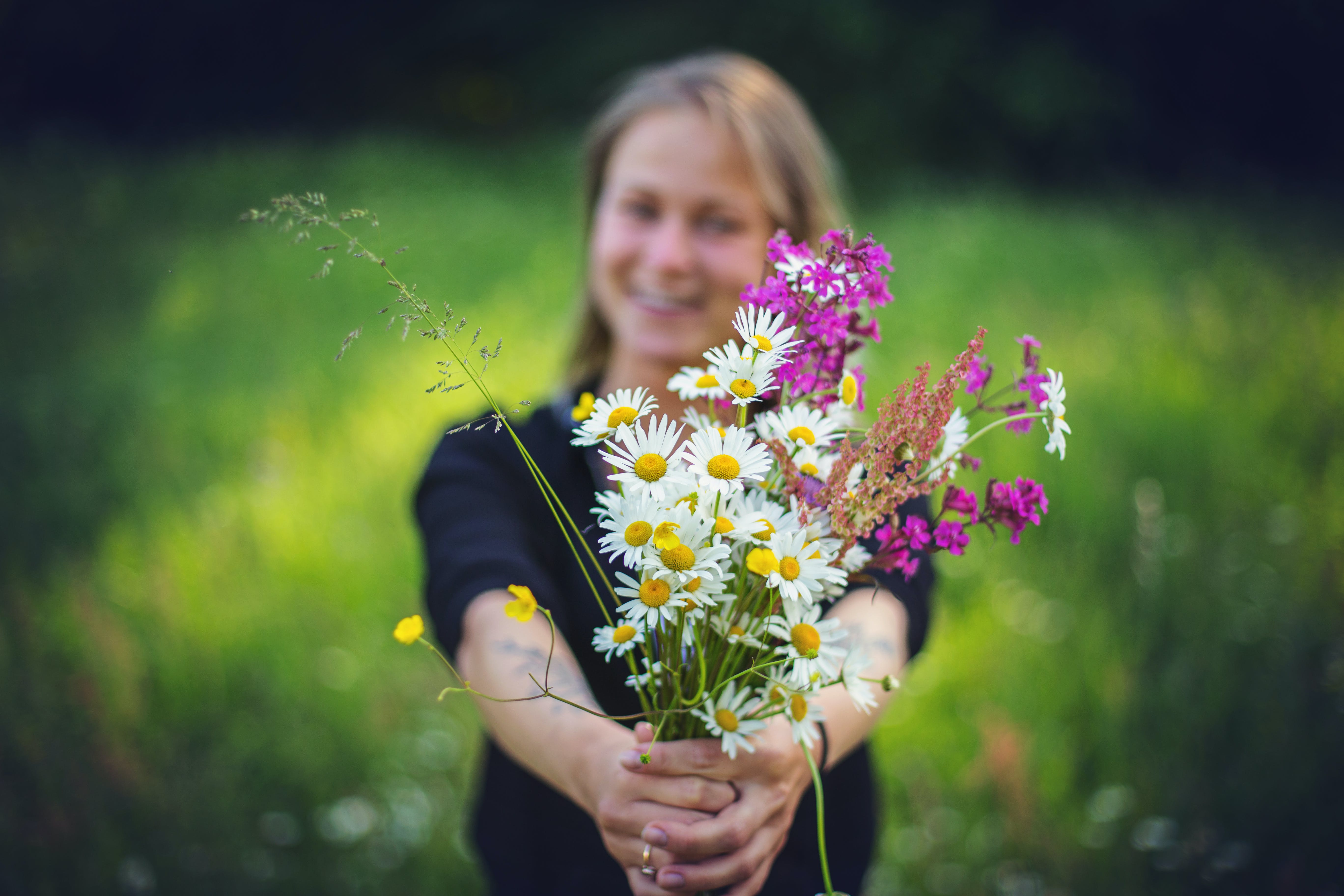 Photography of Woman Holding Flowers