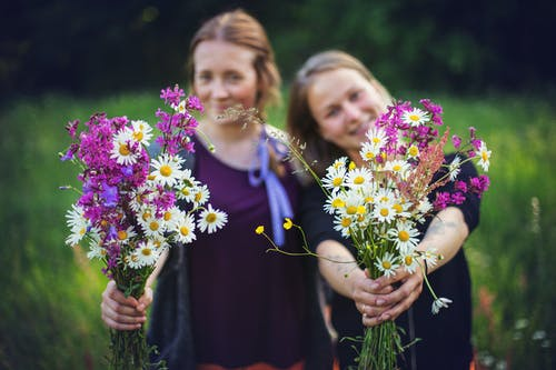 Two Women Holding Flowers