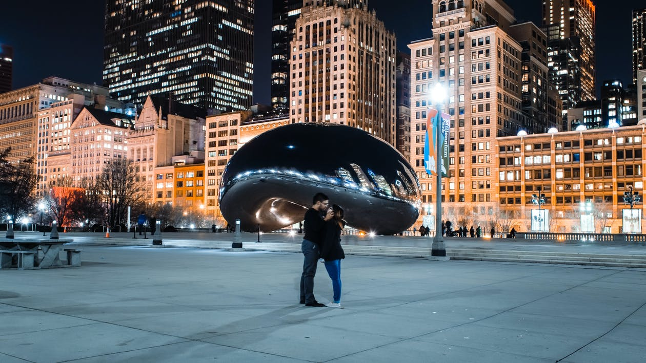 Photo of Standing Couple Kissing In Front of Cloud Gate Sculpture in Chicago, Illinois at Night