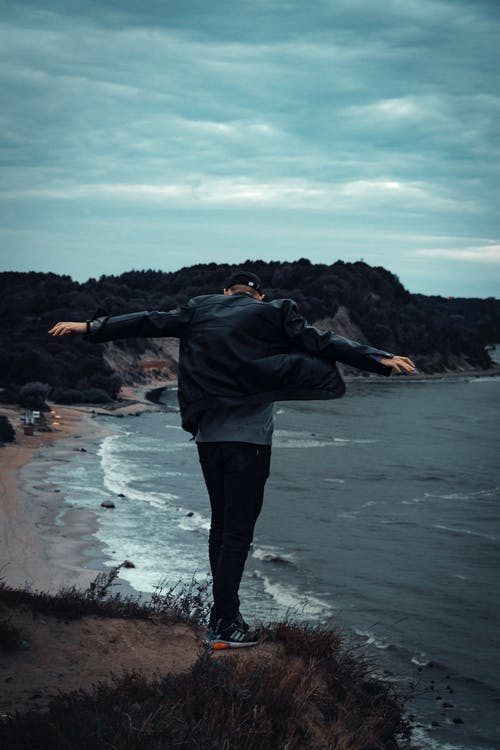 Man Standing On Cliff Facing Body Of Water