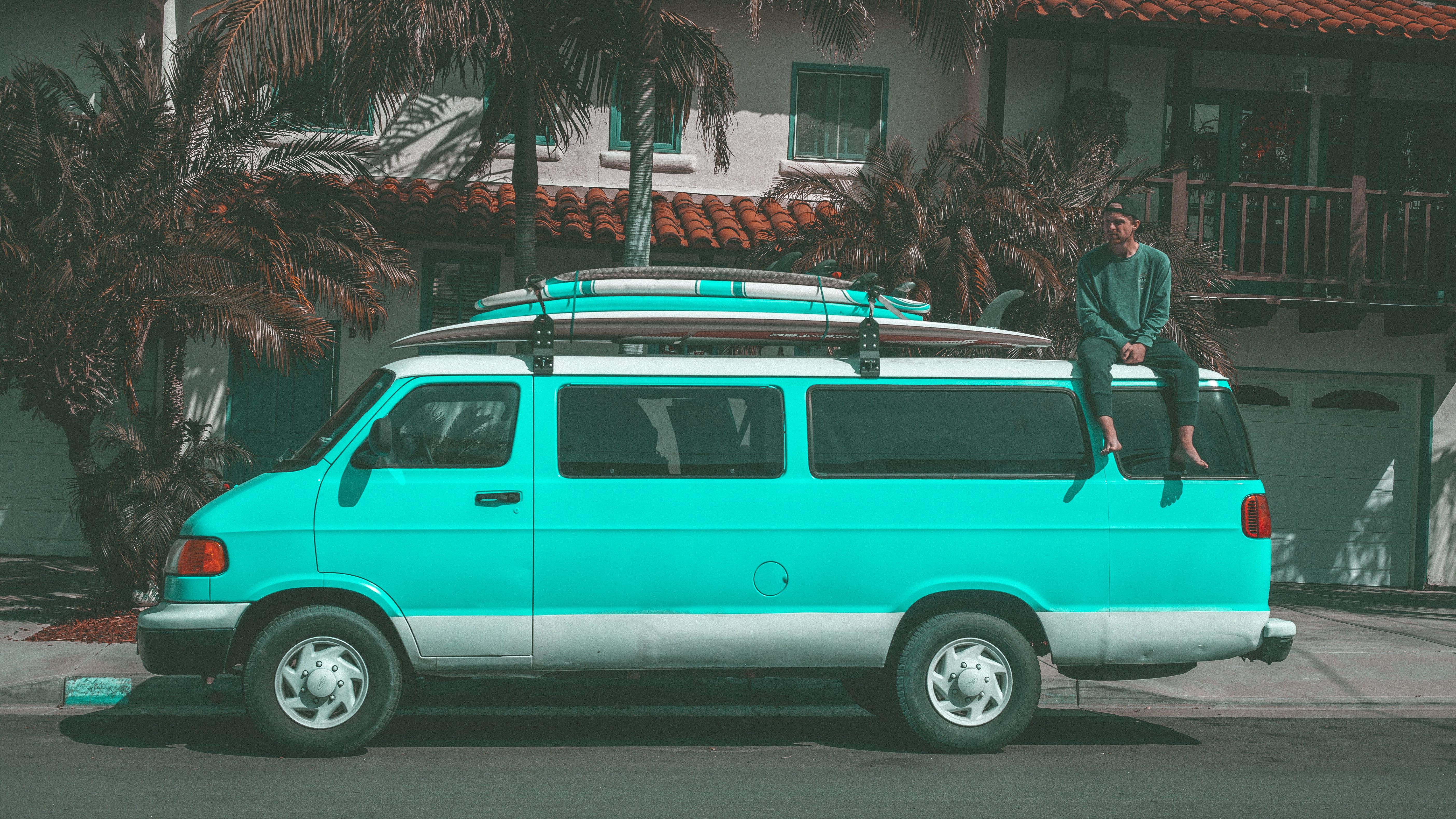 Man Sitting on Top of Teal Dodge Ram Van Parked Near House