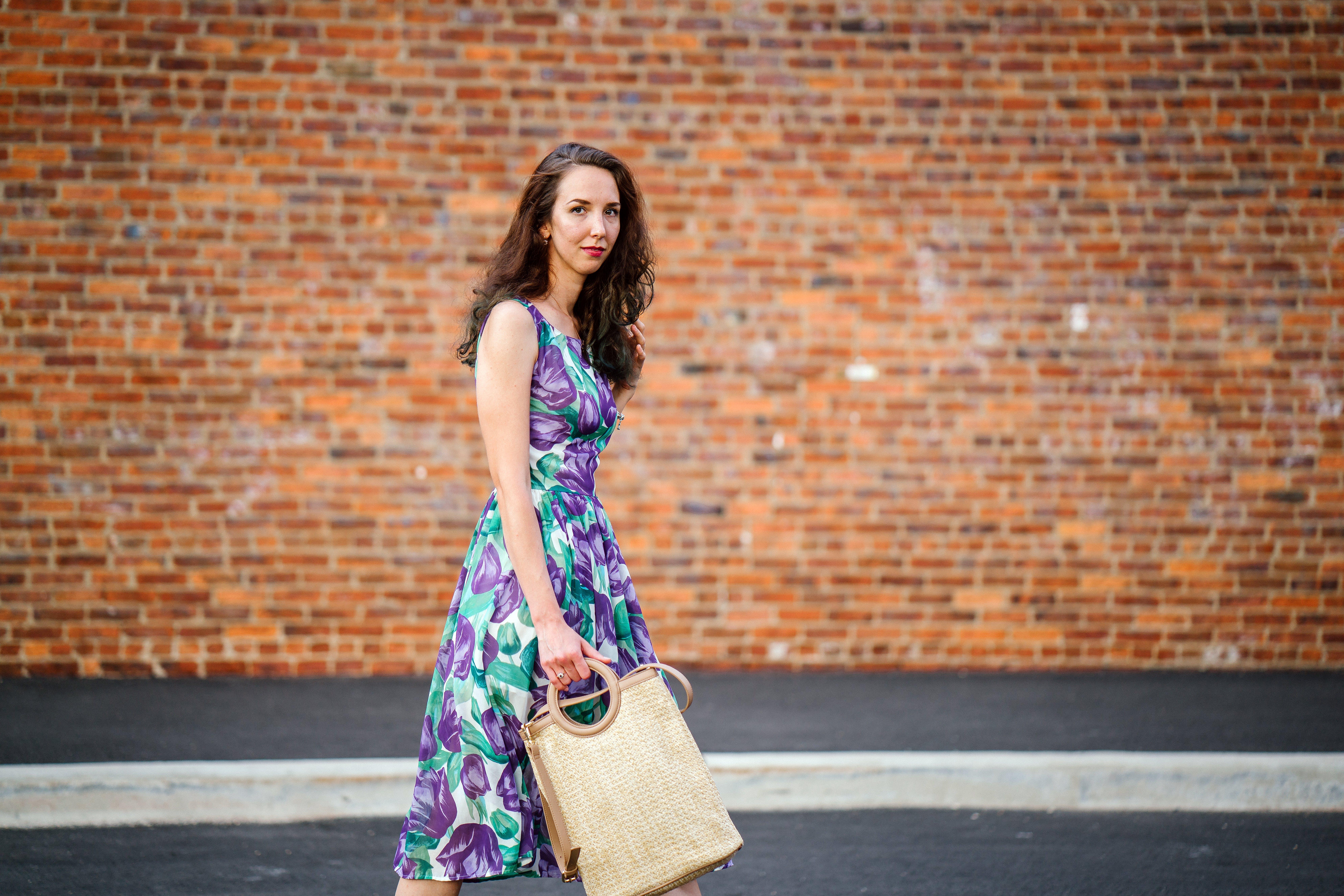 Woman in Purple Floral Dress With Beige Handbag