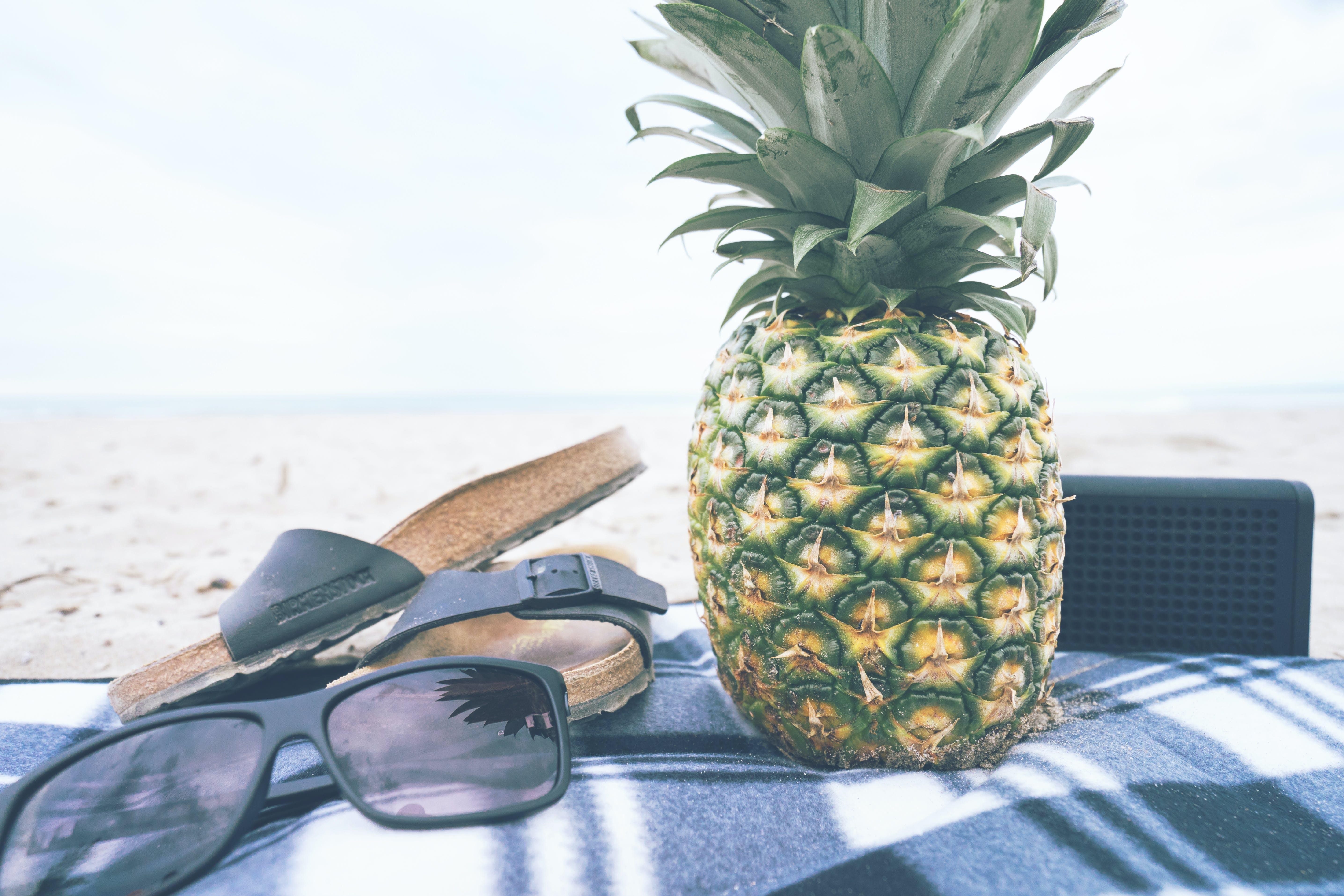 Black Framed Sunglasses Beside Slide Sandals and Pineapple