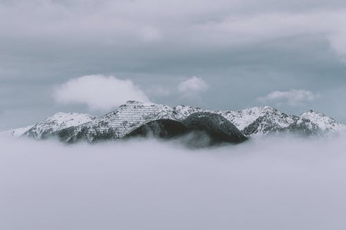 Monochrome Photography Of Mountain Covered by Clouds