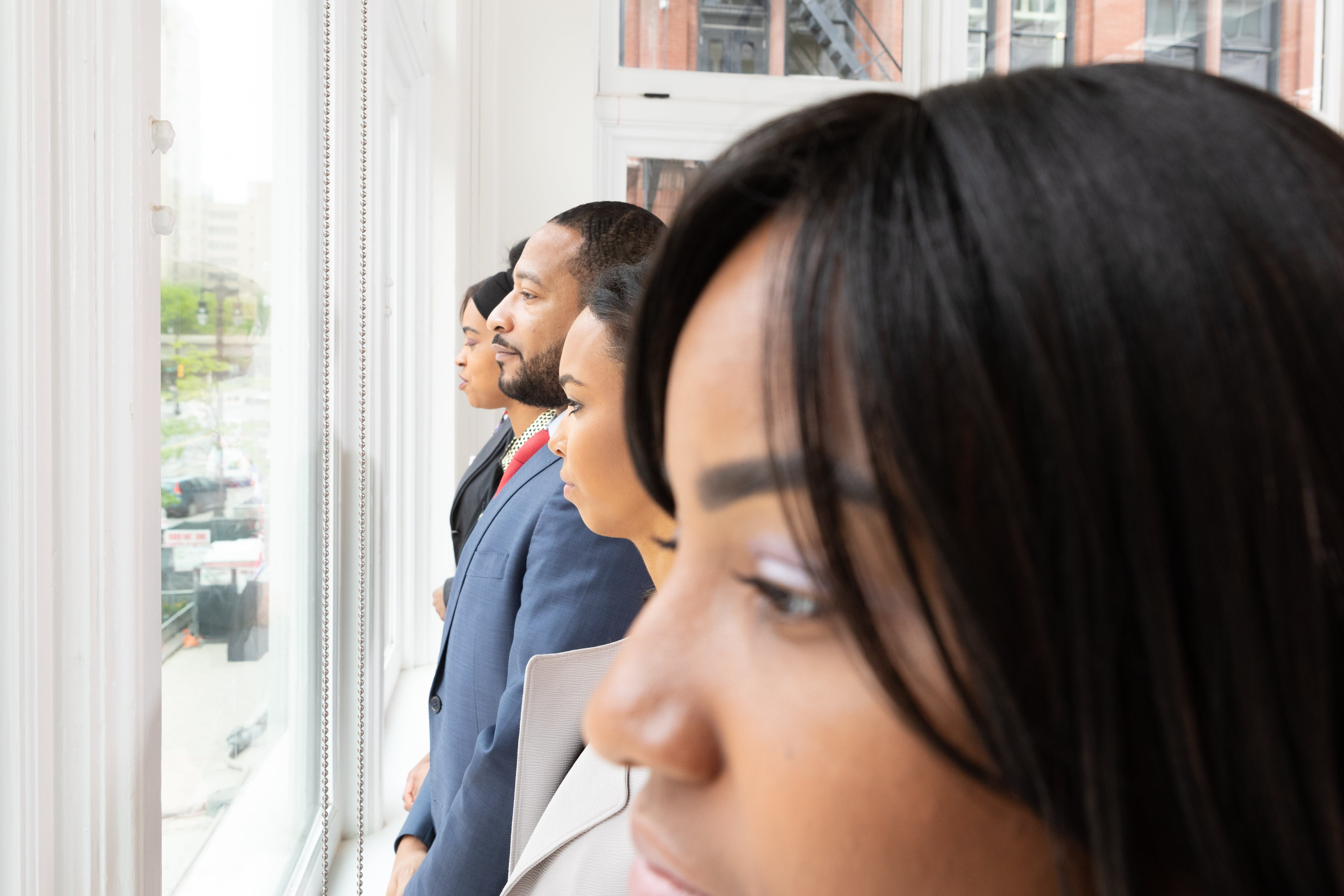 Group Of People Lining Up Near Glass Window