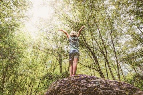 Photo of Girl Standing on Rock Raising Her Hands