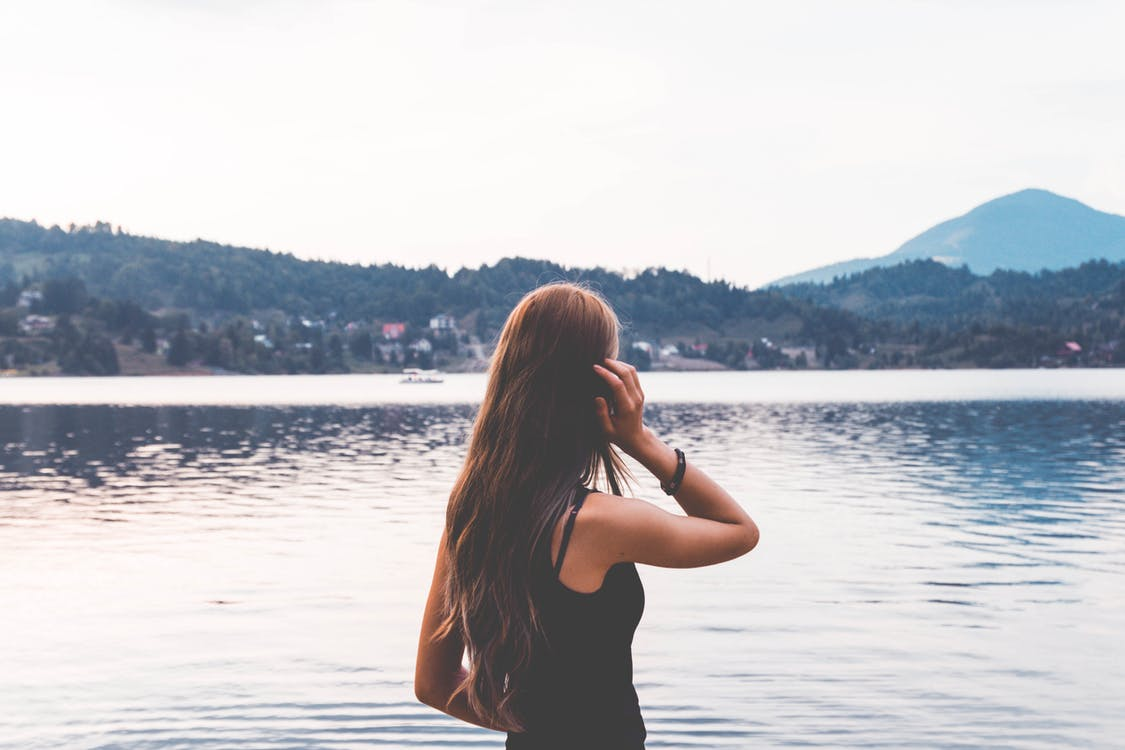 Woman Standing Near Calm Body Of Water