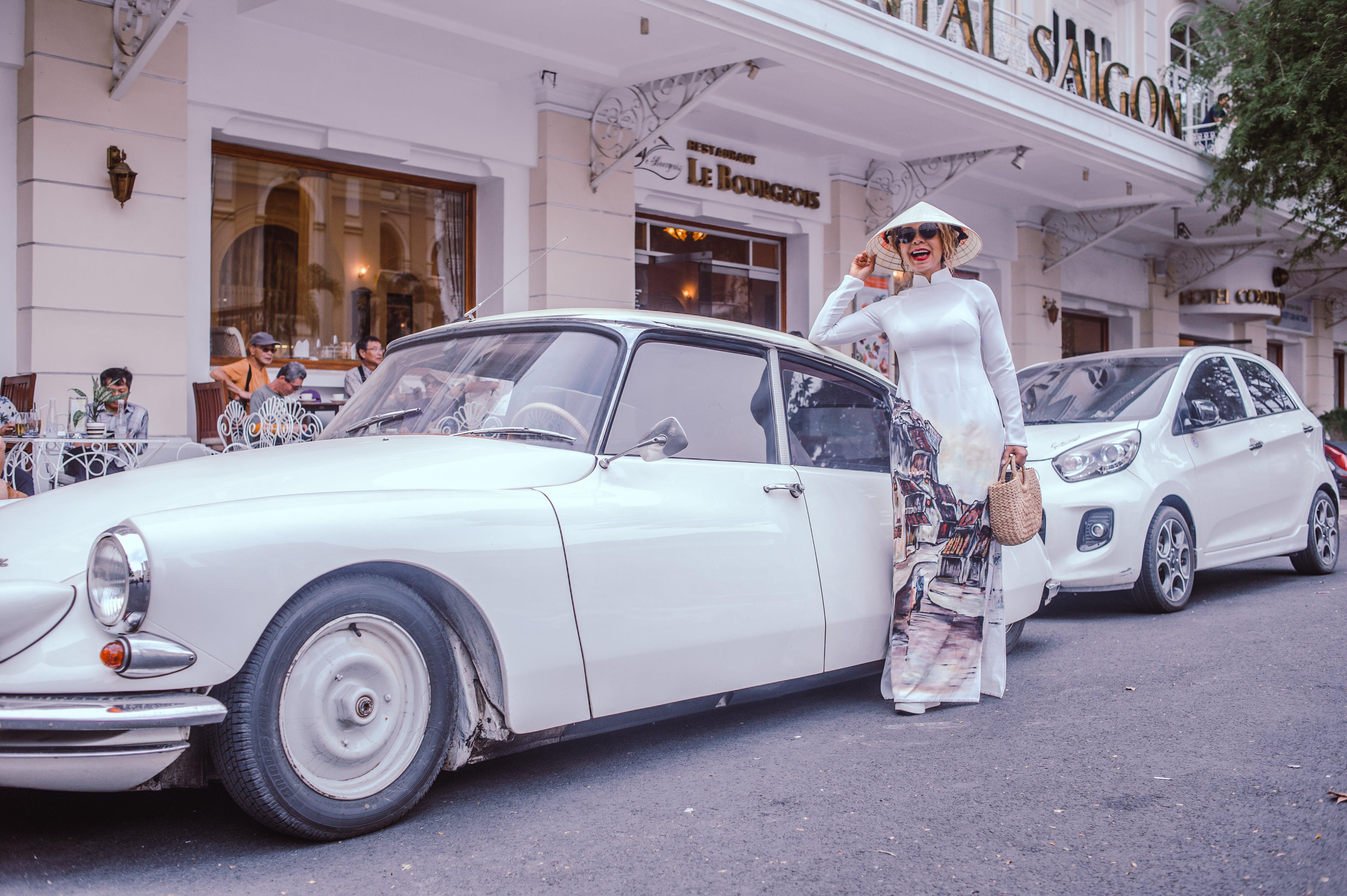 Woman Standing Beside Classic White Sedan
