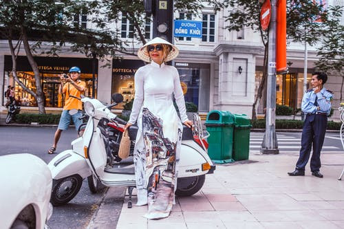 Woman Standing Beside Motor Scooter