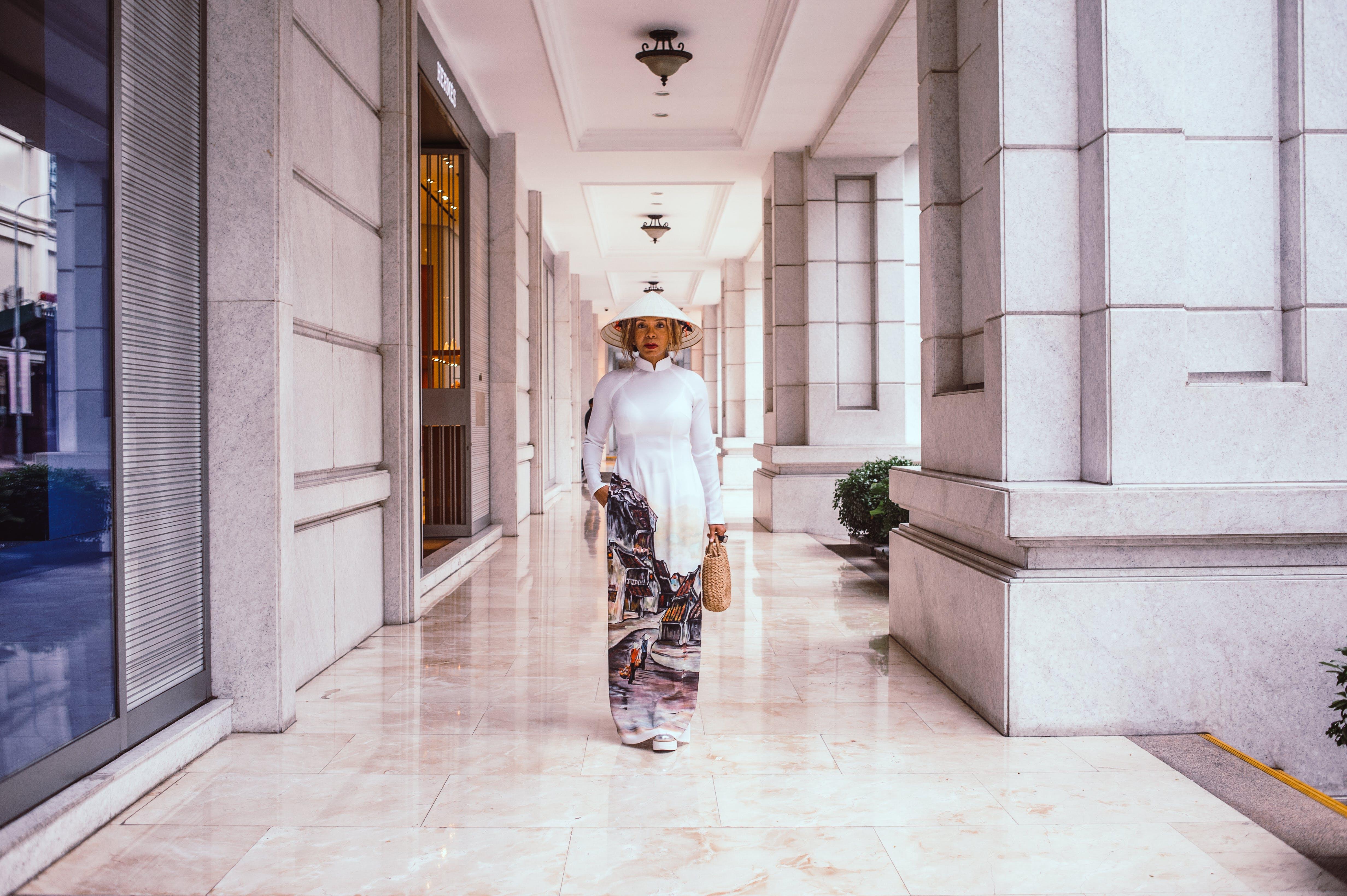 Woman Walking Beside Pillar