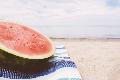 Sliced Water Melon on Textile Near Seashore