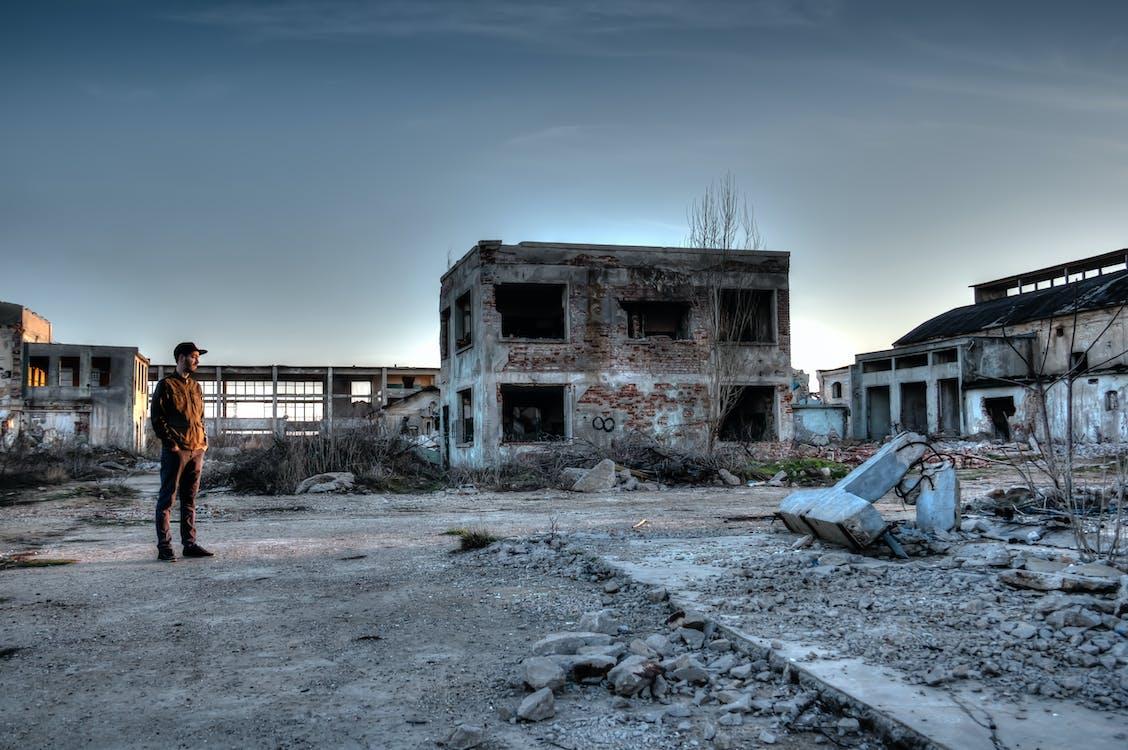 Man Standing Near Ruined Buildings