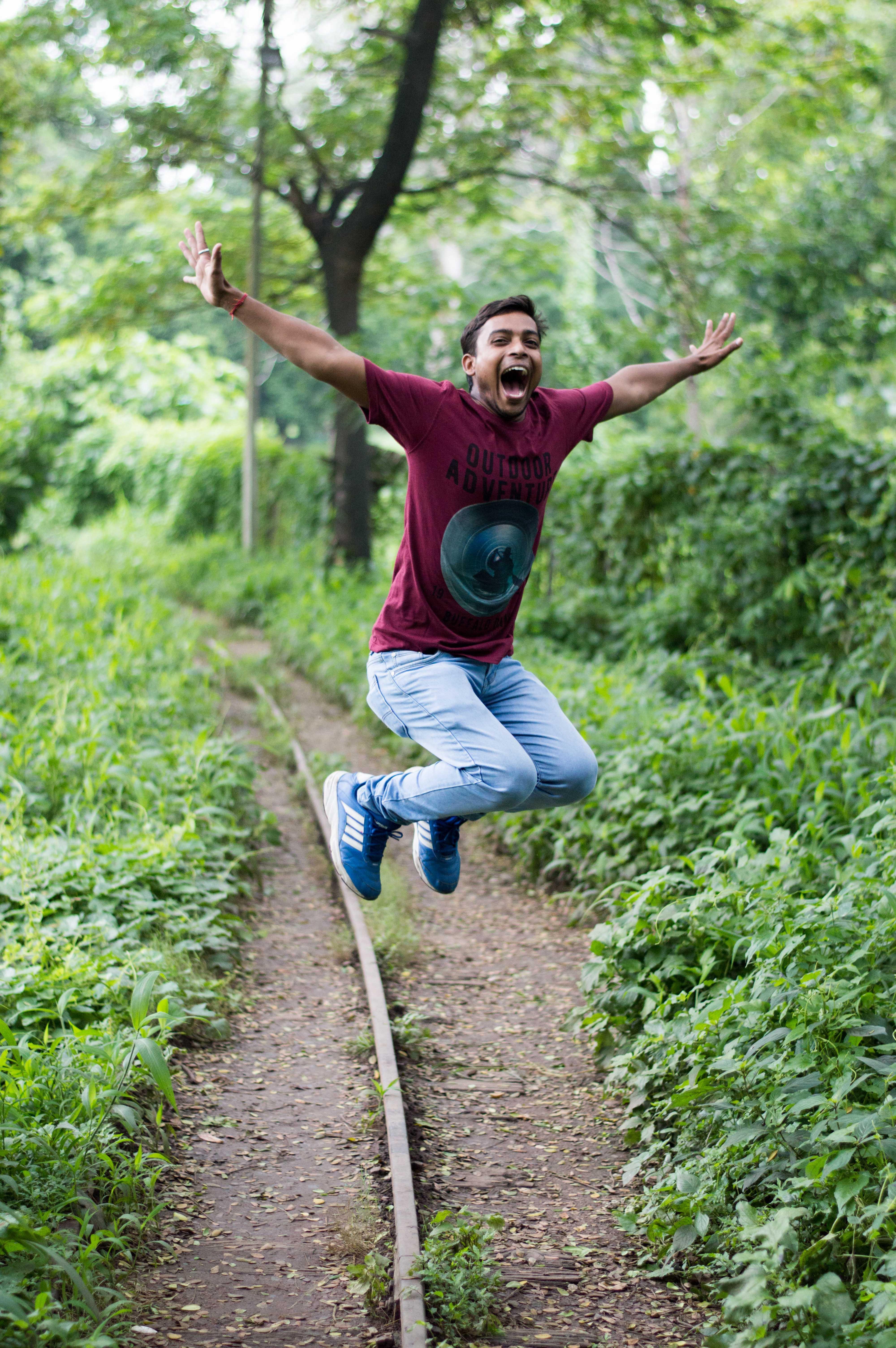 Jump Shot Photo of Man Near Tree