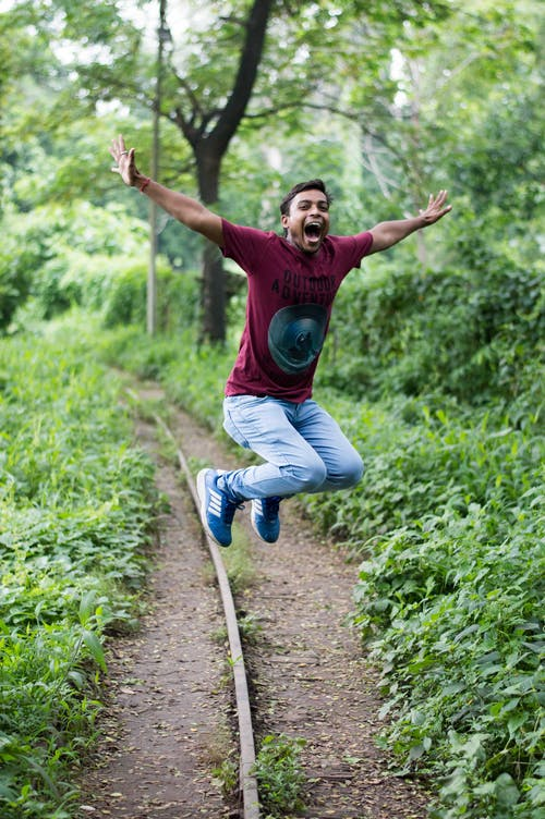 Jump Shot Photo of Man Near Tree