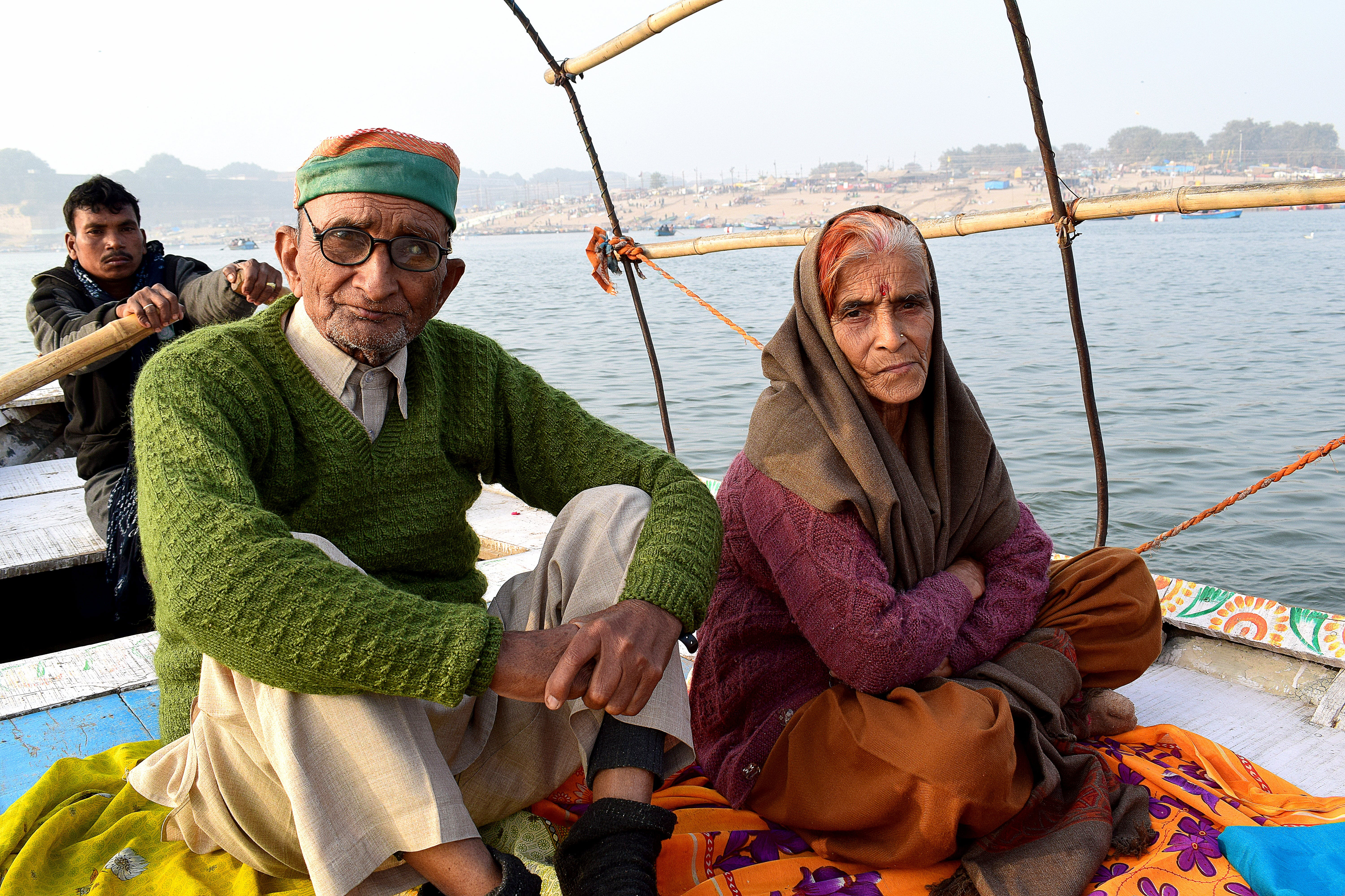 Man and Woman Sitting on Boat Under White Clouds