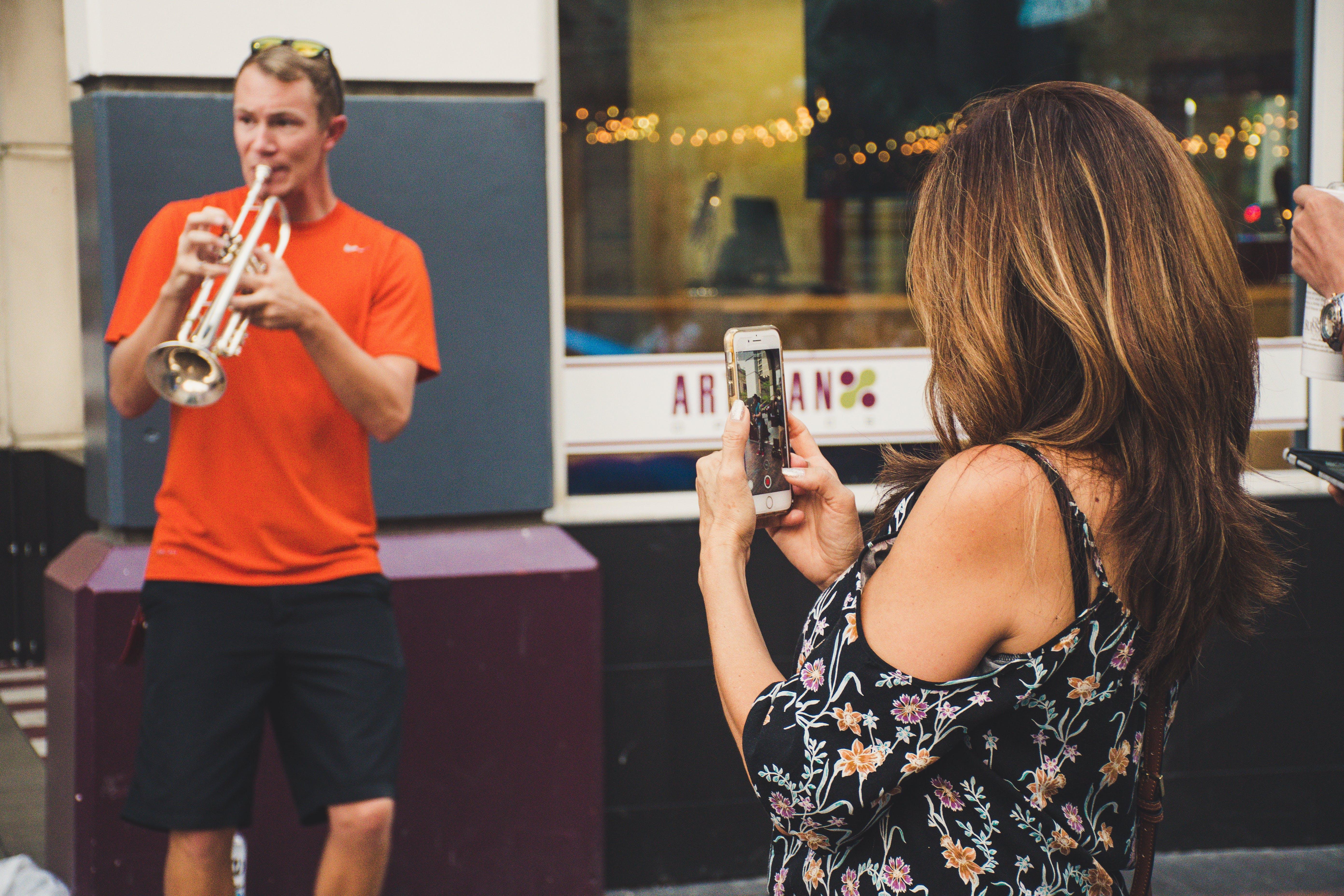 Woman Taking Photo of Man Playing Trumpet