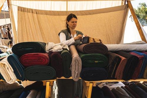 Woman Putting Bag Above Fabrics