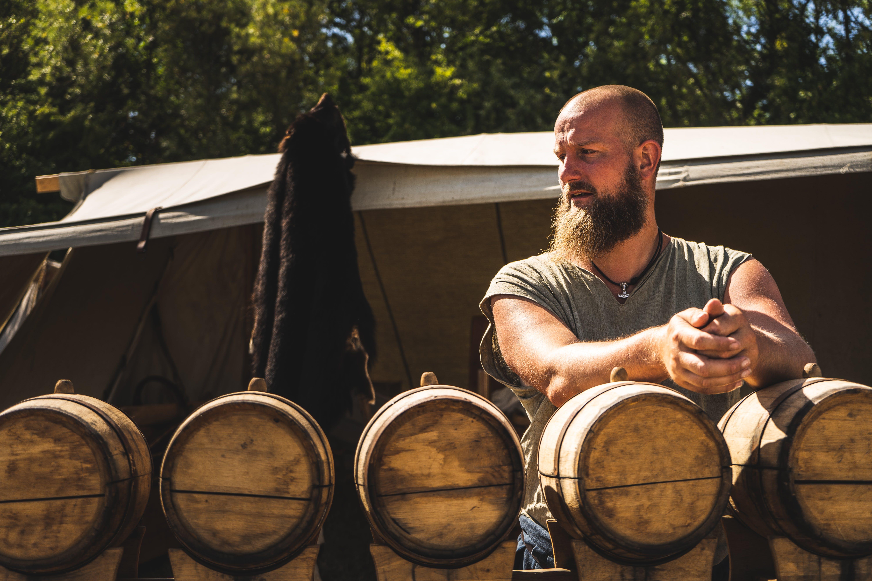 Man Standing in Front of Oak Barrels