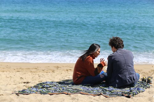 Man and Woman Sitting Near Beach