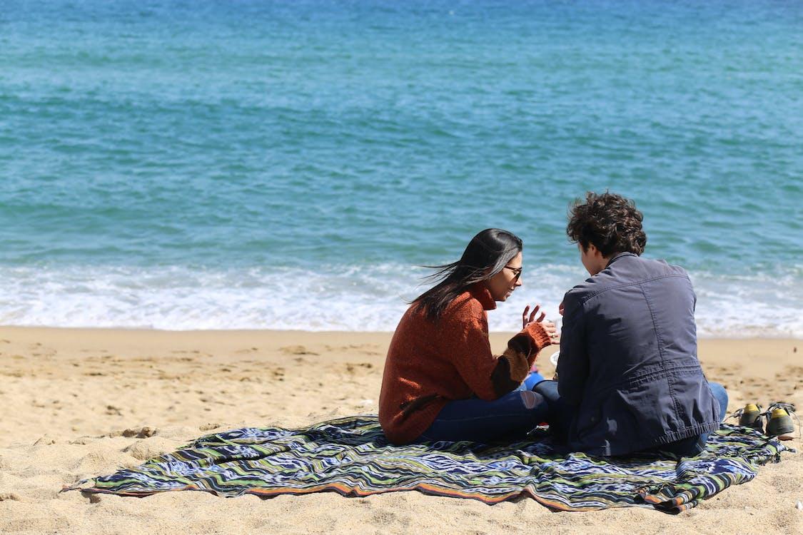 Man and Woman Sitting Near Beach