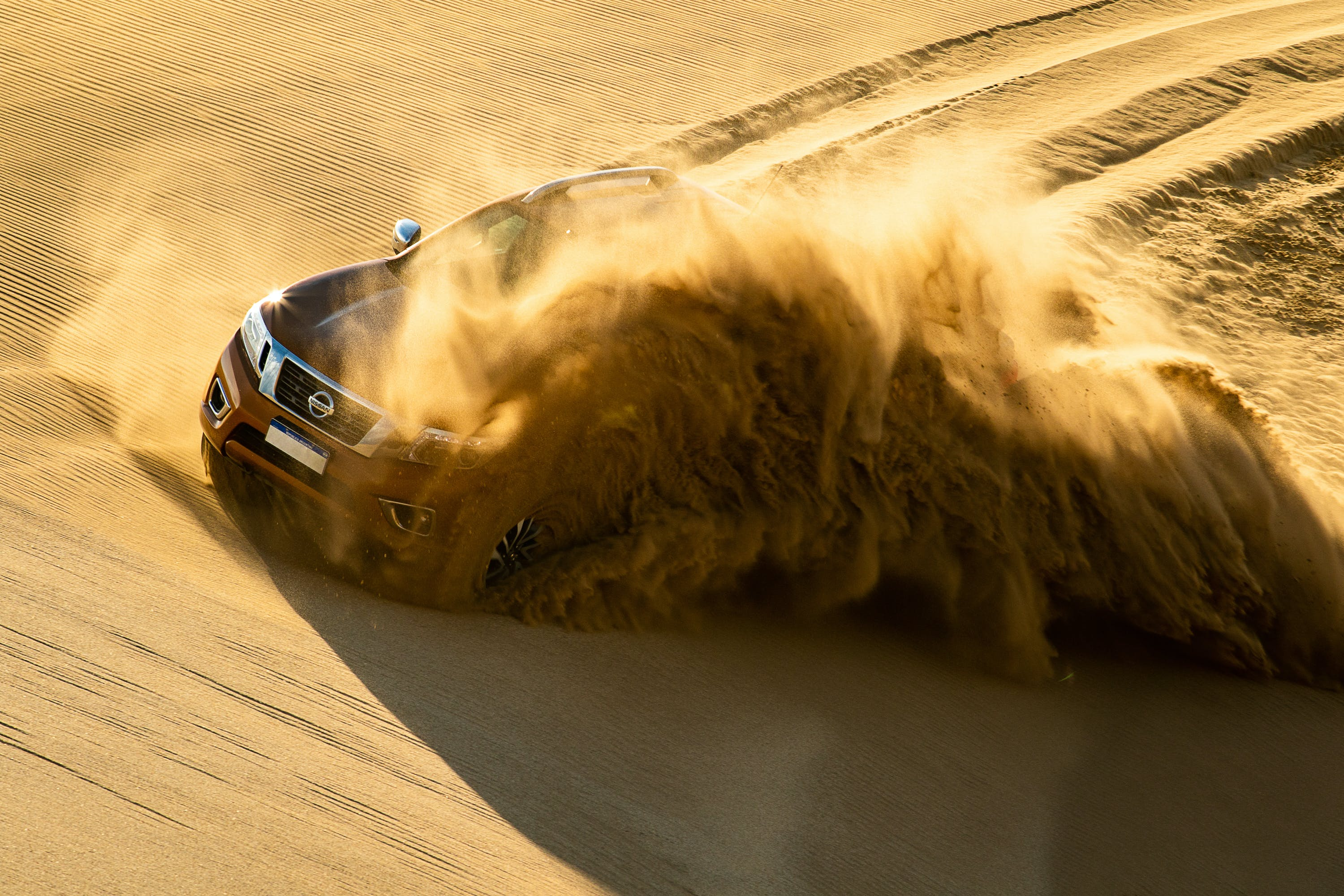 Red Nissan Vehicle Running on Sand Dune
