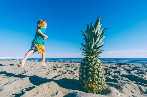 Child Running on Sand Near Bod of Water and Pineapple
