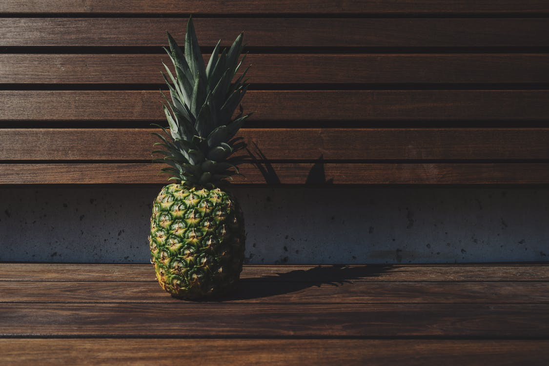 Green Pineapple on Brown Wooden Bench \