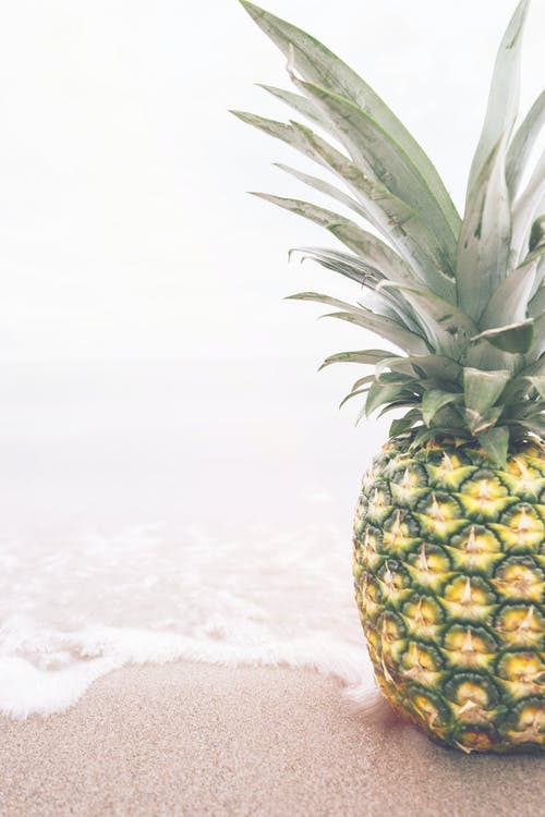 Green and Yellow Pineapple on Sand