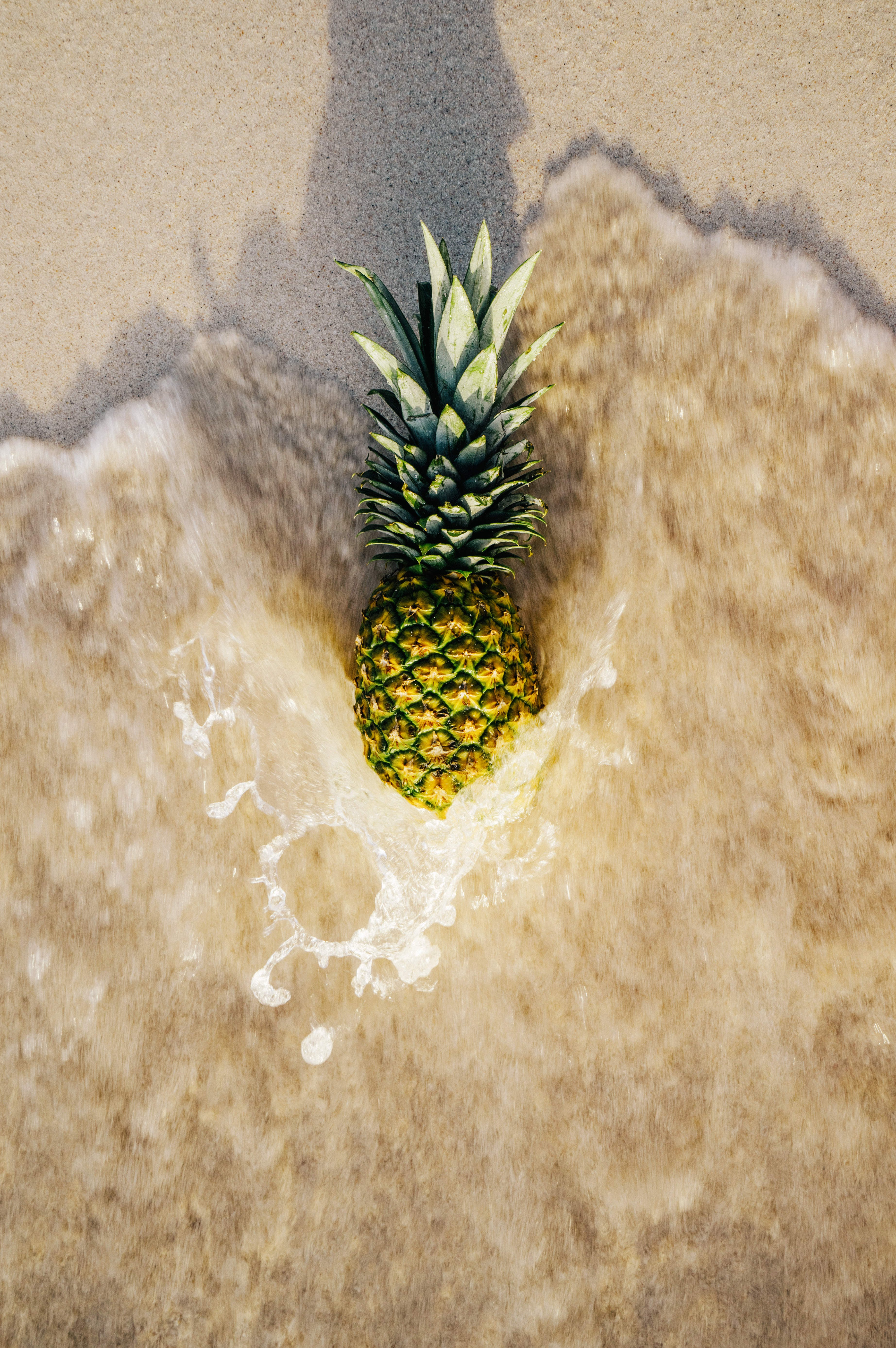Pineapple on Sand Touched by Water