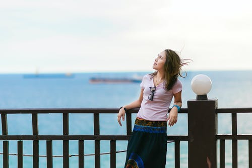 Woman Resting Beside Brown Steel Fence Looking at Sky