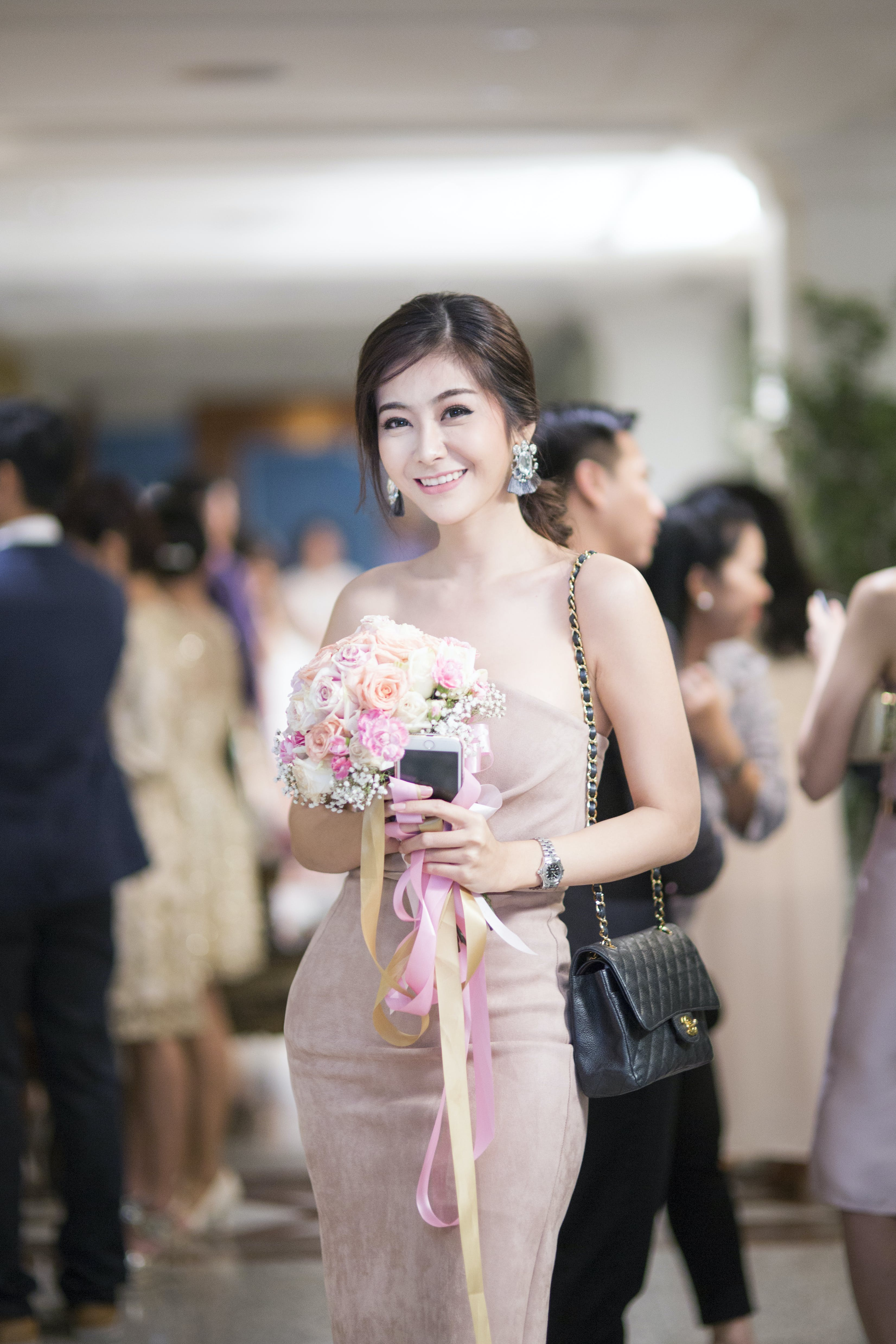 Woman in Pink Strapless Bodycon Dress Holding Flowers