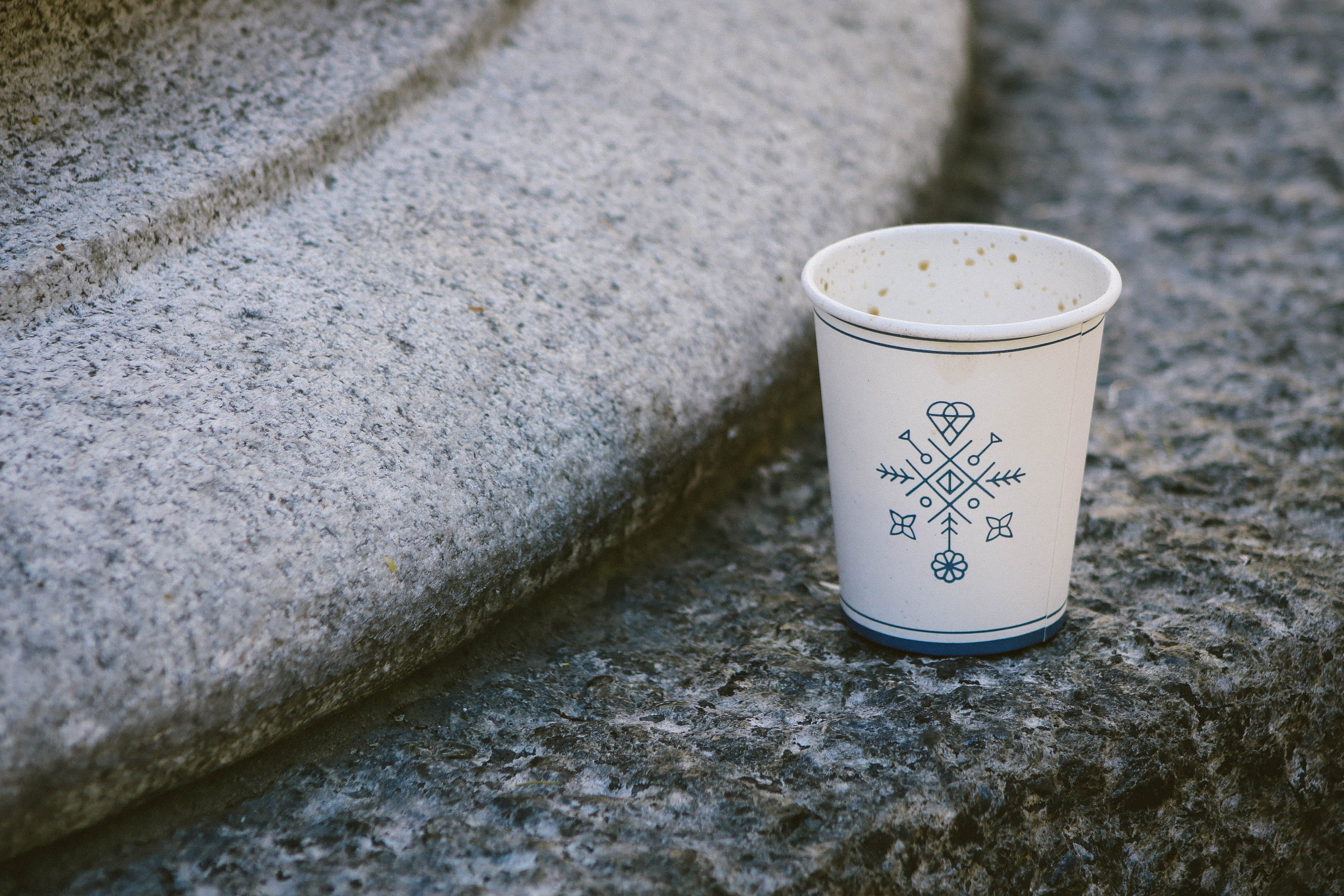 White Disposable Cup On Concrete Surface