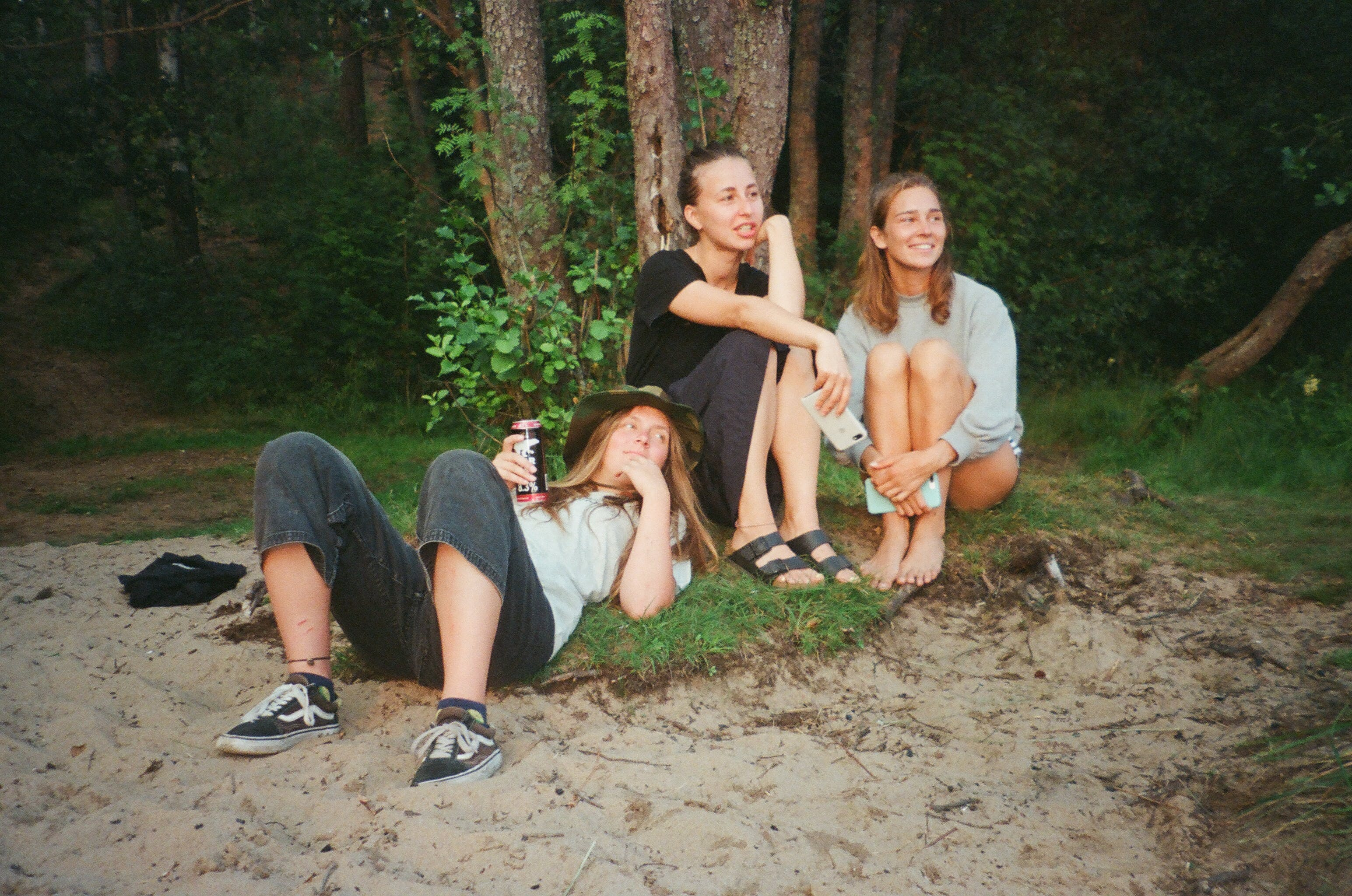 Three Women Relaxing Infront of Trees