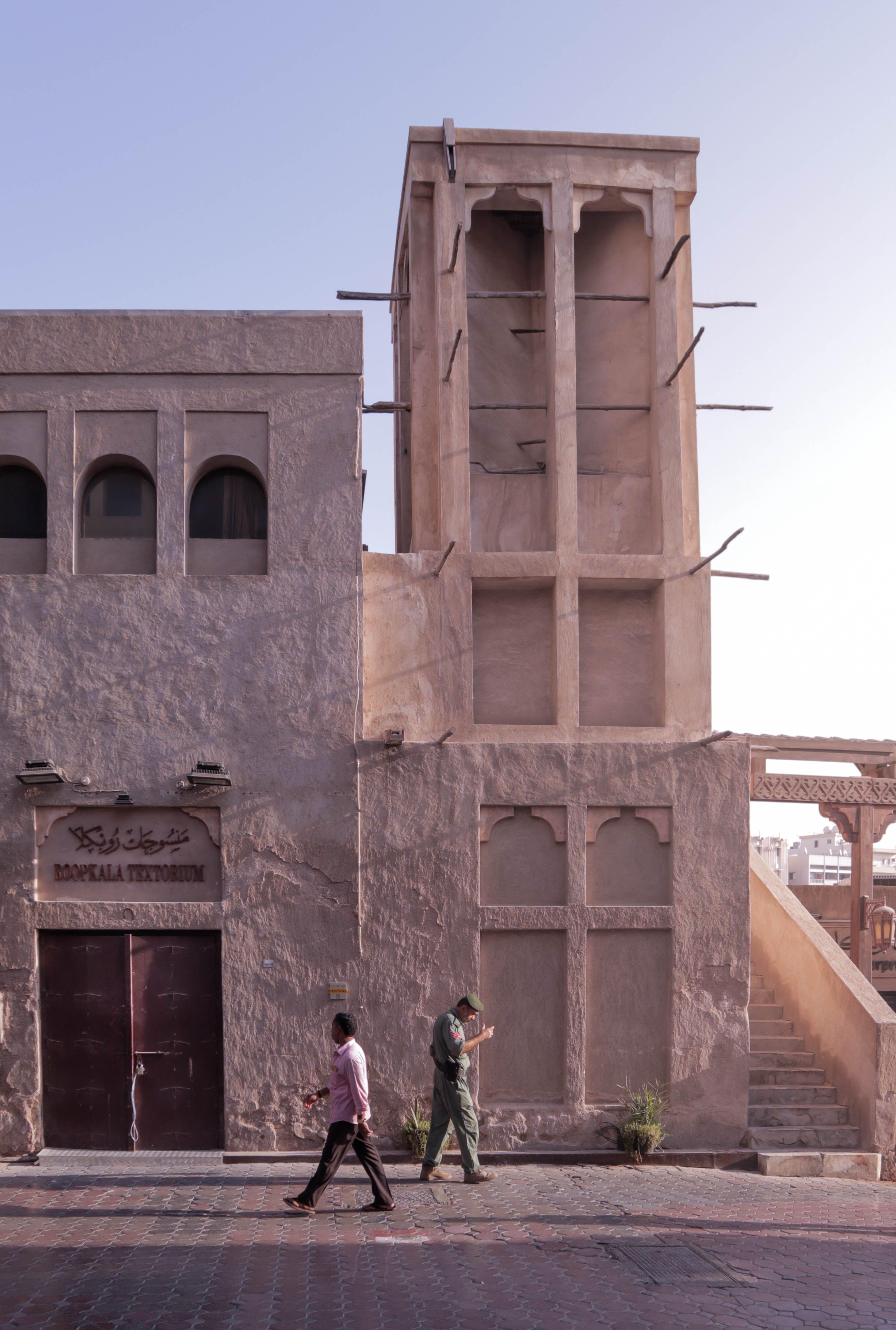 Two People Walking Beside White Building
