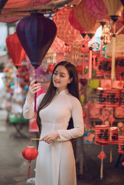 Woman Holding Paper Lantern Beside Store