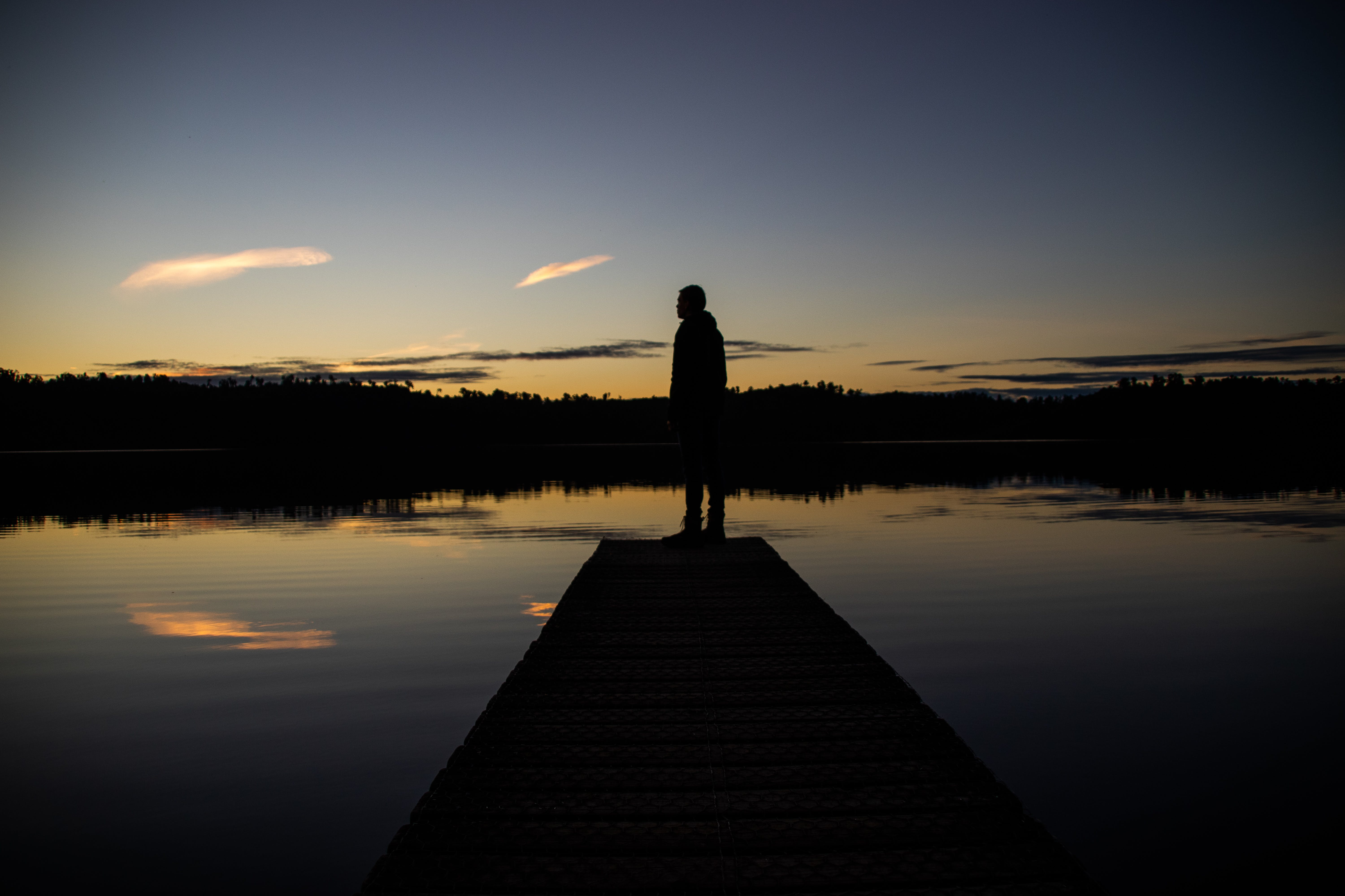 Silhouette of Person Standing on Body of Water Dock during Sunrise
