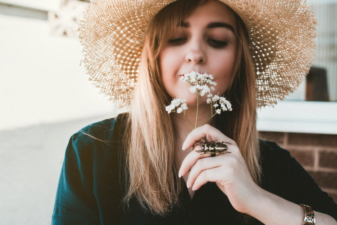 Woman Wearing Brown Sun Hat Smelling White Flowers