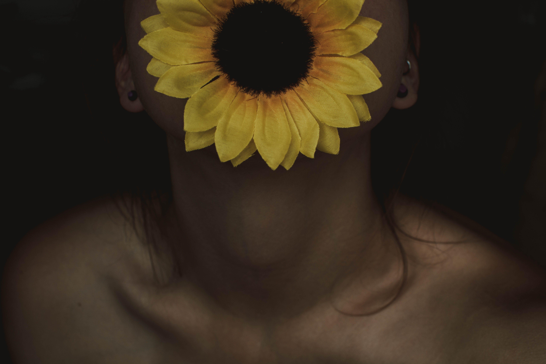 Woman Biting Sunflower on Black Background